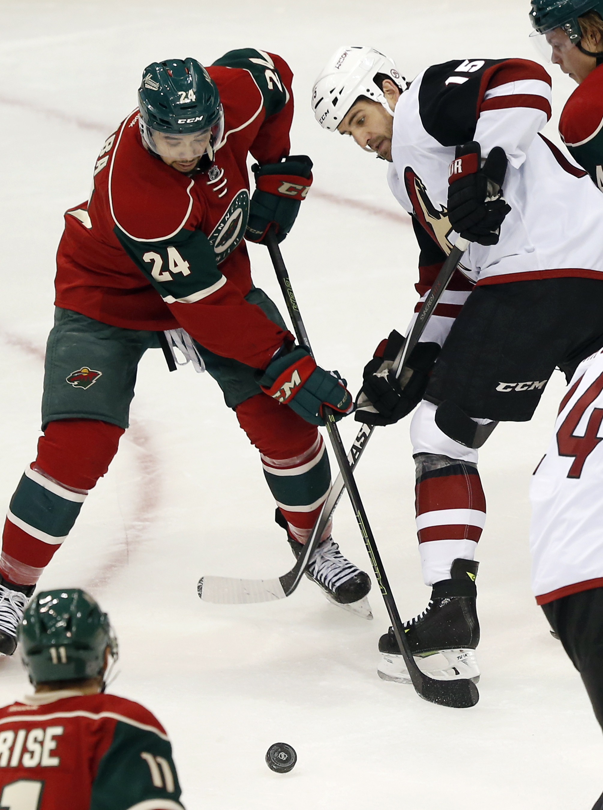 Minnesota Wild's Matt Dumba, left, tries to keep Arizona Coyotes' Boyd Gordon away from the puck in the first period  of an NHL hockey game, Monday, Jan. 25, 2016, in St. Paul, Minn. (AP Photo/Jim Mone)