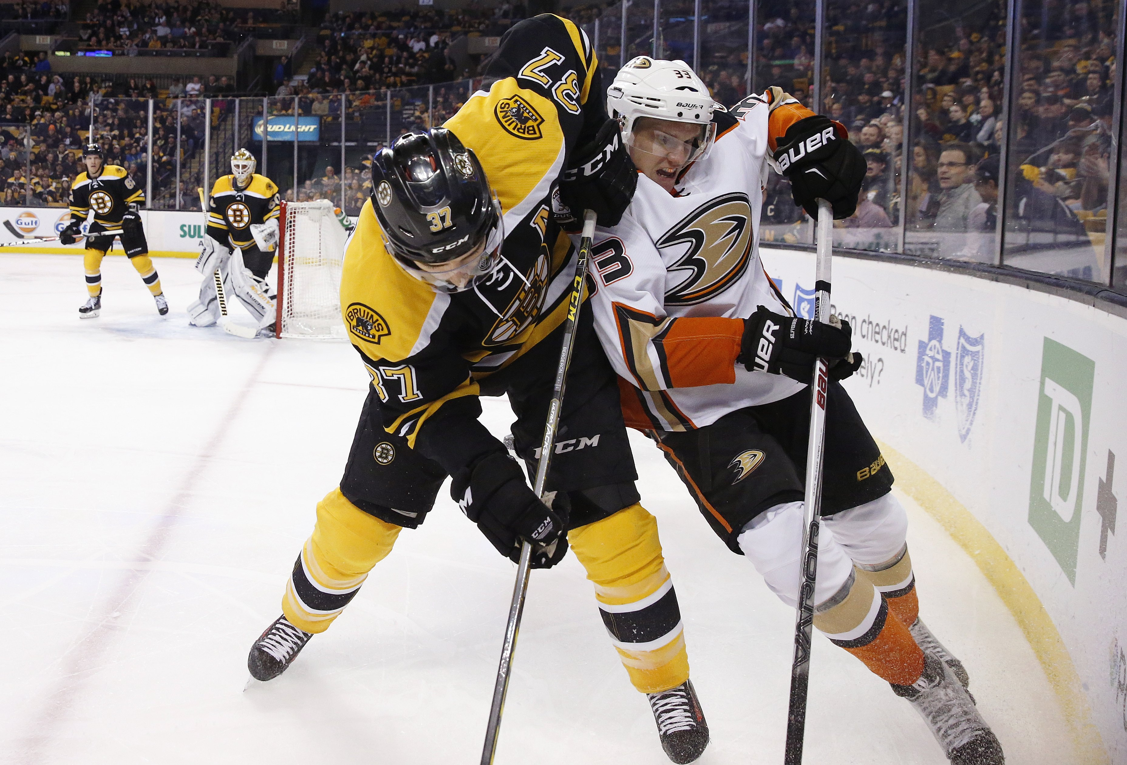 Boston Bruins' Patrice Bergeron (37) and Anaheim Ducks' Jakob Silfverberg (33) battle for the puck during the first period of an NHL hockey game in Boston, Tuesday, Jan. 26, 2016. (AP Photo/Michael Dwyer)