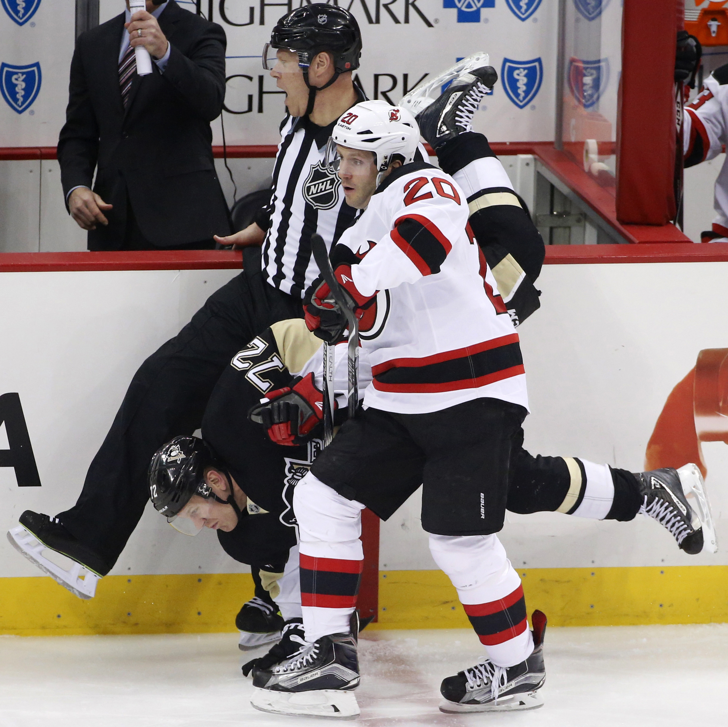 New Jersey Devils' Lee Stempniak (20) and Pittsburgh Penguins' Patric Hornqvist (72) collide with linesman Scott Driscoll during the first period of an NHL hockey game in Pittsburgh, Tuesday, Jan. 26, 2016. (AP Photo/Gene J. Puskar)