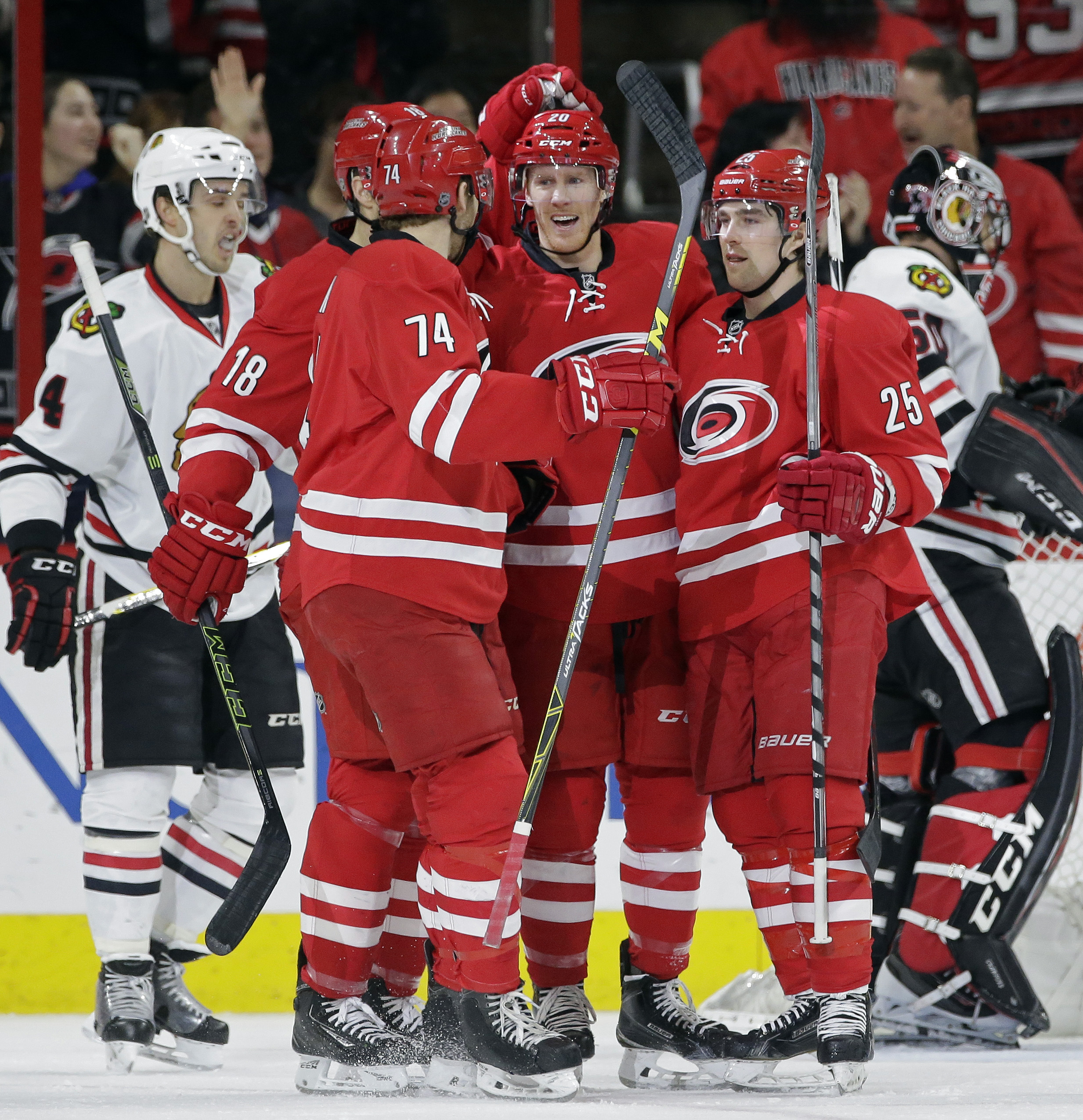 Carolina Hurricanes' Riley Nash (20) is congratulated by Hurricanes' Jay McClement (18), Jaccob Slavin (74) and Chris Terry (25) following Nash's goal against Chicago Blackhawks goalie Corey Crawford, right, during the first period of an NHL hockey game i