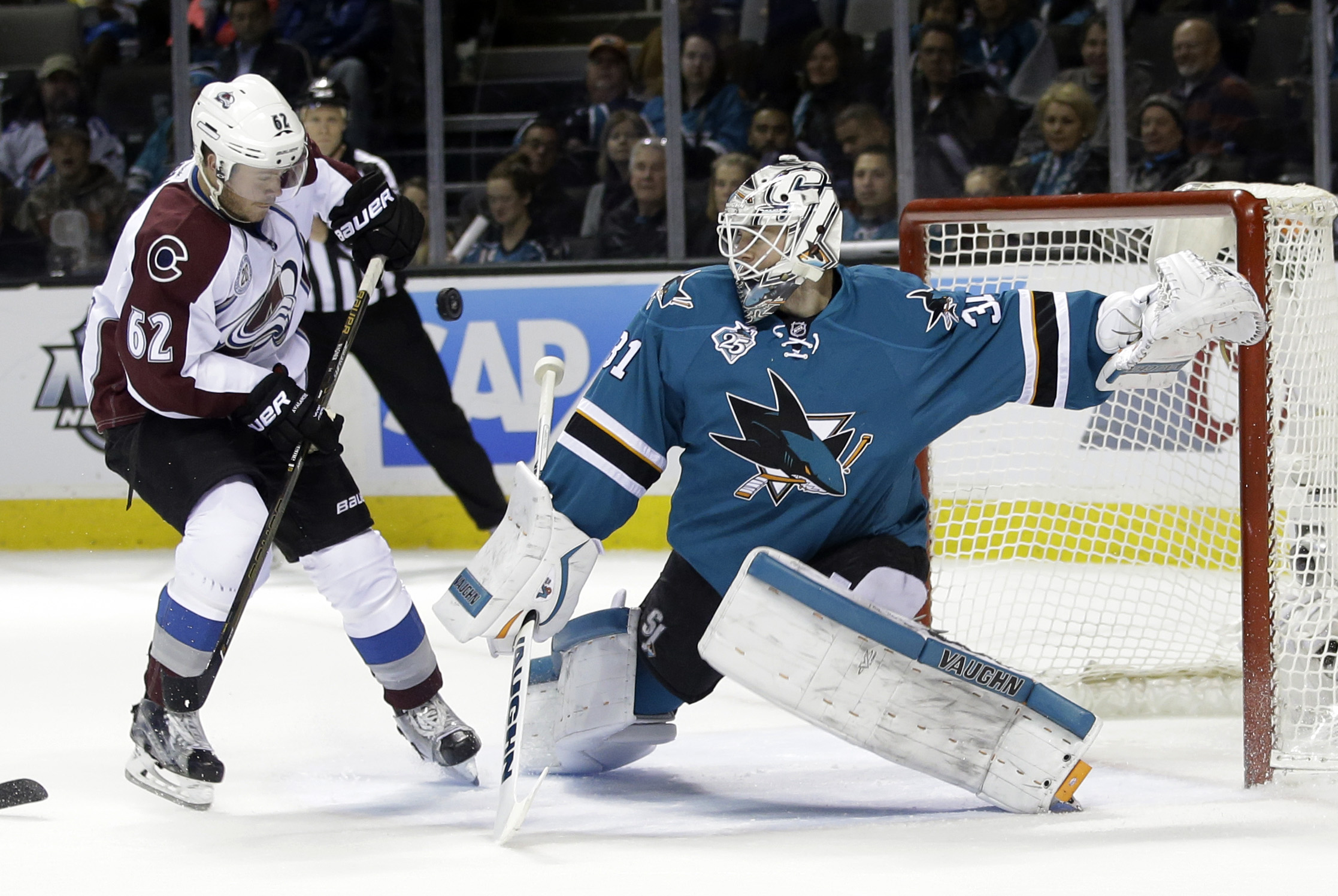 San Jose Sharks goalie Martin Jones, right, deflects a shot on goal as Colorado Avalanche's Chris Wagner (62) closes in during the second period of an NHL hockey game Tuesday, Jan. 26, 2016, in San Jose, Calif. (AP Photo/Marcio Jose Sanchez)