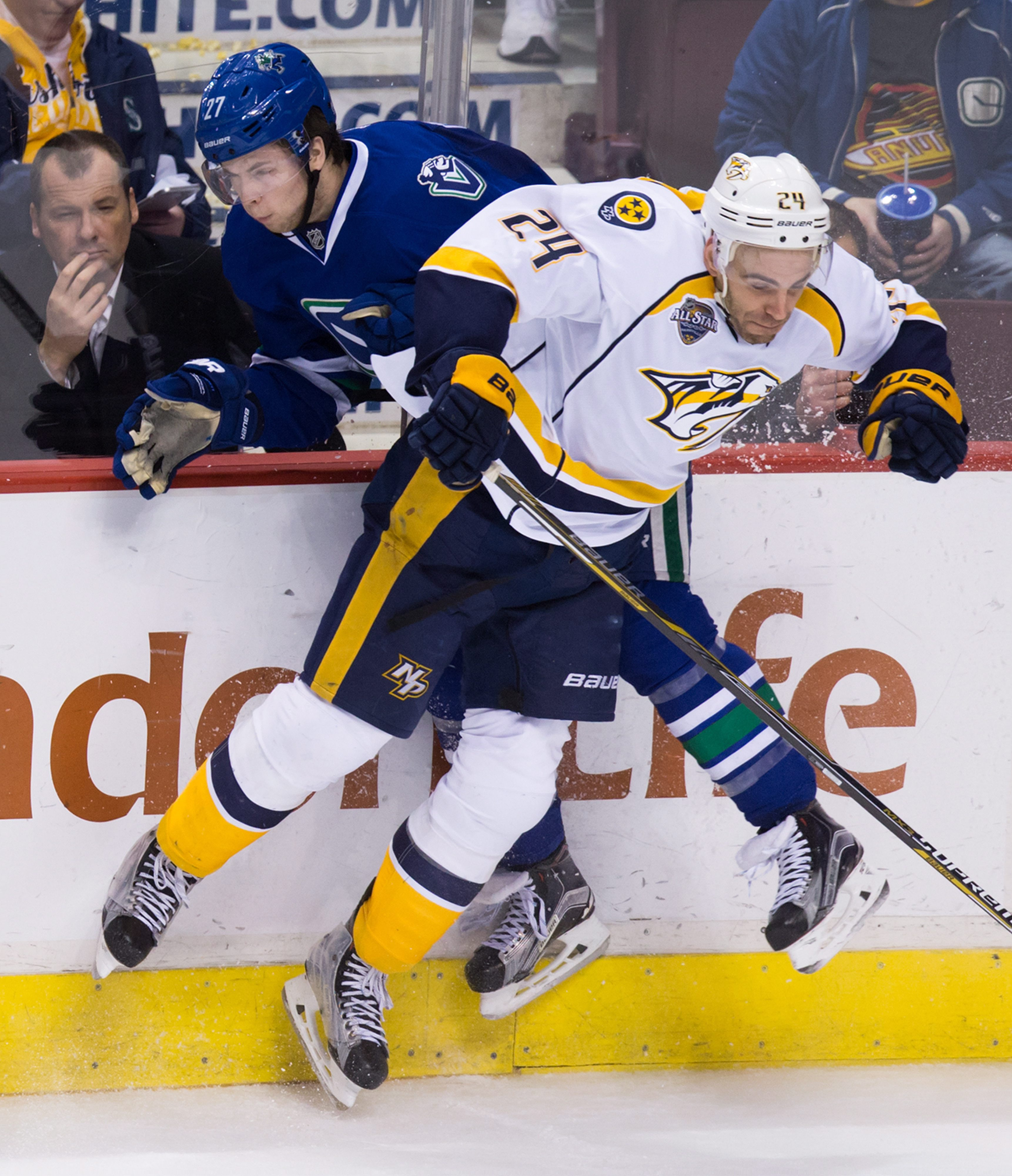 Vancouver Canucks' Ben Hutton, back, and Nashville Predators' Eric Nystrom collide during the third period of an NHL hockey game Tuesday, Jan 26, 2016, in Vancouver, British Columbia. (Darryl Dyck/The Canadian Press via AP)