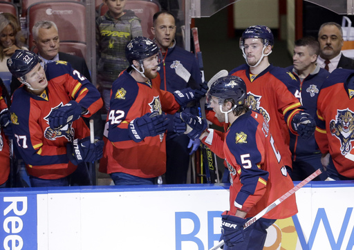 FILE - In this Jan. 22, 2016 file photo, Florida Panthers defenseman Aaron Ekblad (5) is congratulated by teammates after scoring a goal against the Chicago Blackhawks during the second period of an NHL hockey game in Sunrise, Fla. On a team with a soon-t