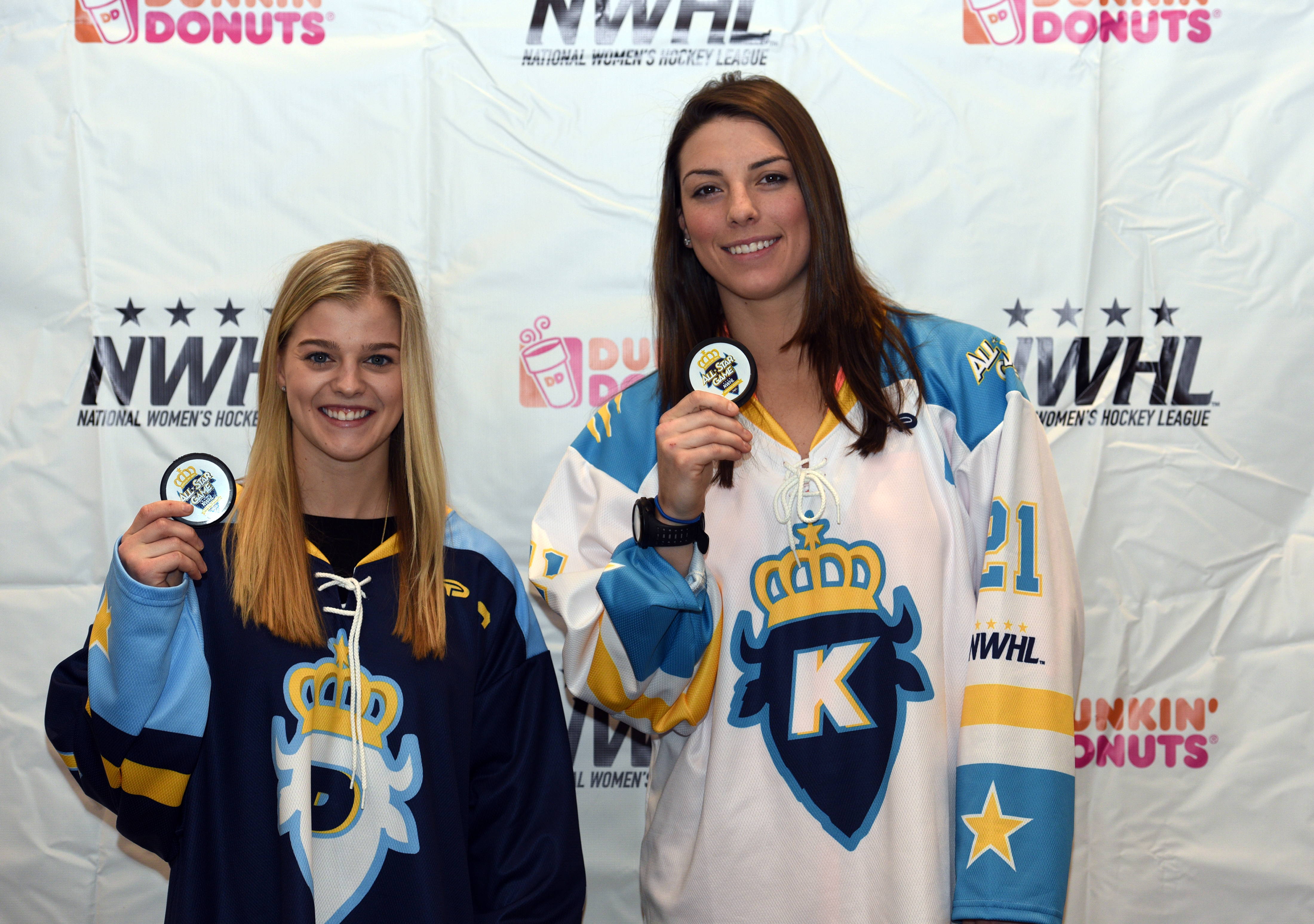 In this Saturday, Jan. 23, 2016, photo, National Women's Hockey League All-Star captains Hilary Knight, left, and Emily Pfalzer pose holding game pucks in Buffalo, N.Y. In just its first year, the upstart U.S.-based NWHL beat it's longer-established, Cana