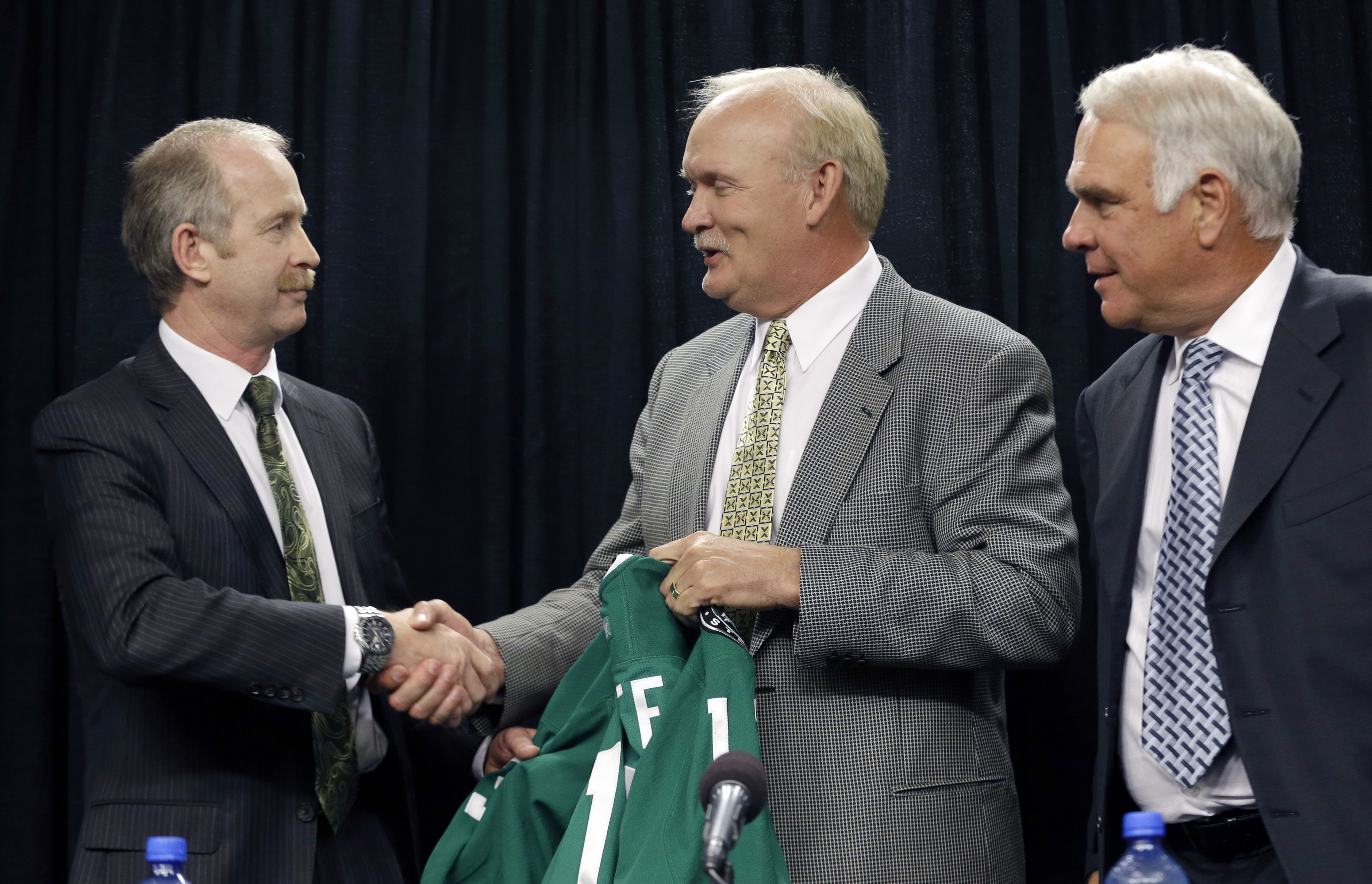 FILE - In this June 21, 2013, file photo, Dallas Stars' new hockey coach Lindy Ruff, center, shakes hands with with general manager Jim Nill, left, as president Jim Lites looks on during an NHL hockey news conference in Dallas. Jim Nill had a 10-year plan