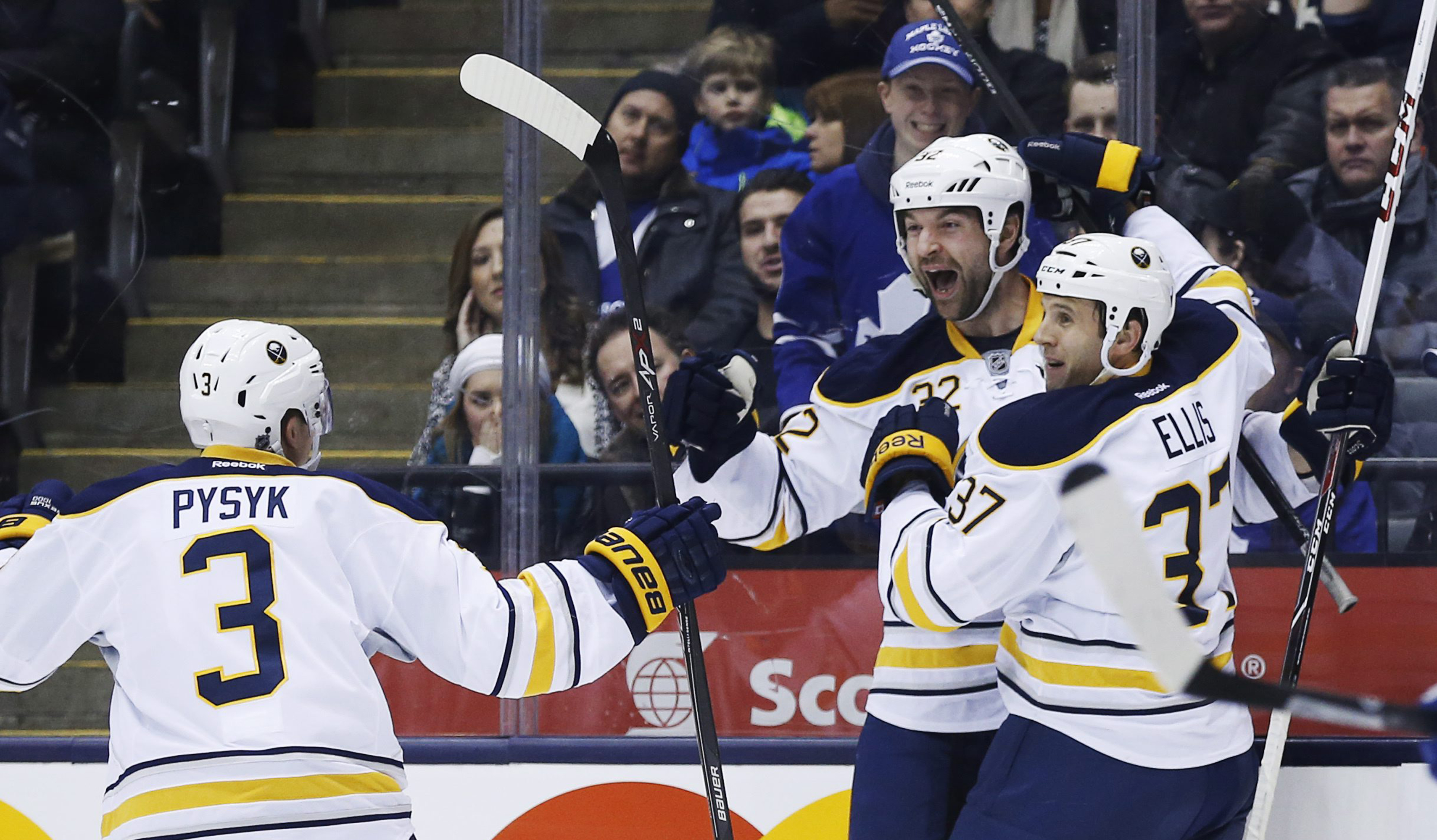 Buffalo Sabres' John Scott, center, celebrates his goal with teammates Mark Pysyk, left, and Matt Ellis against the Toronto Maple Leafs during the first period of an NHL hockey game Friday, Dec. 27, 2013, in Toronto. Scott took a shot at the NHL in a firs