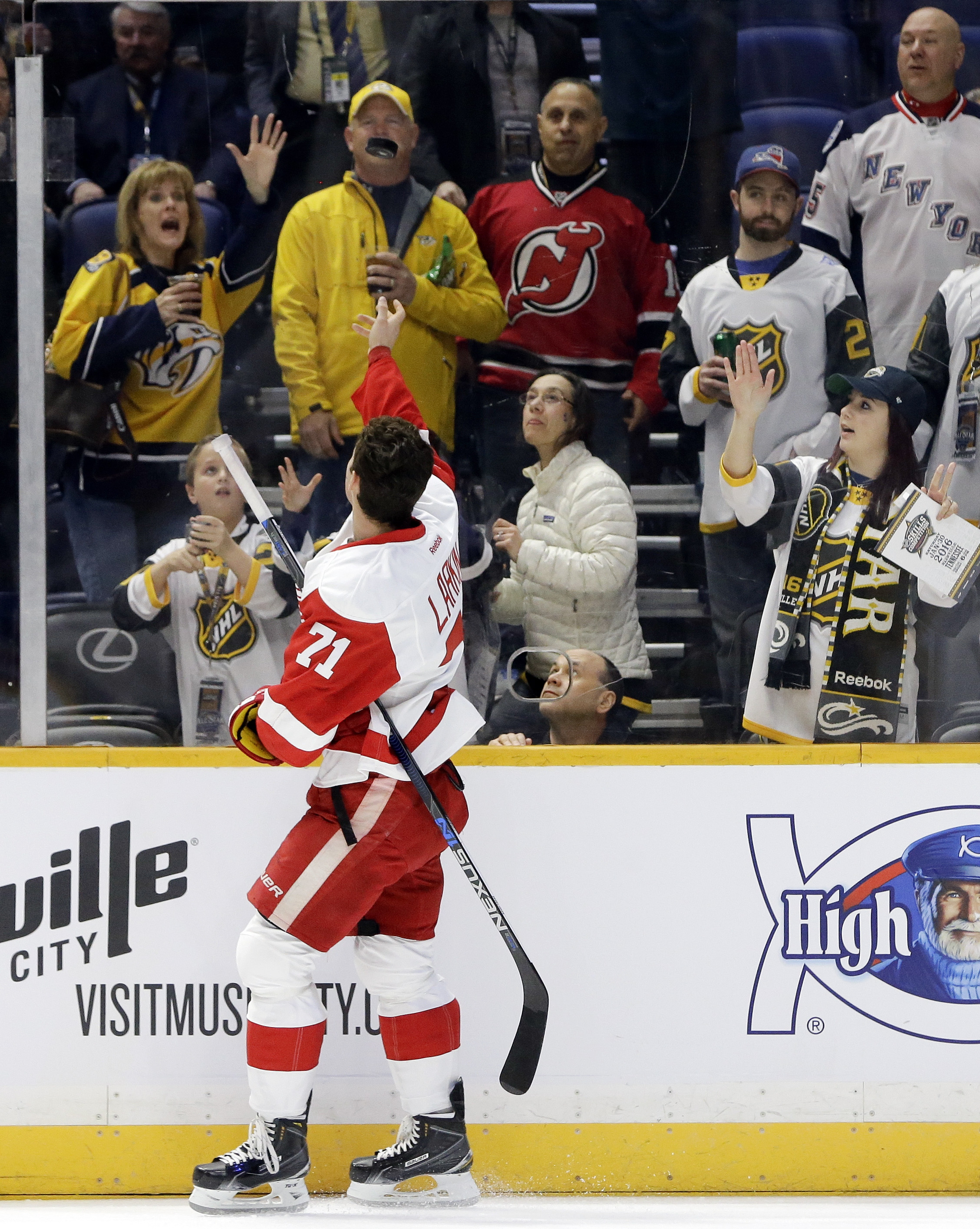 Detroit Red Wings forward Dylan Larkin (71) tosses a puck to fans before the NHL hockey All-Star game skills competition Saturday, Jan. 30, 2016, in Nashville, Tenn. (AP Photo/Mark Humphrey)