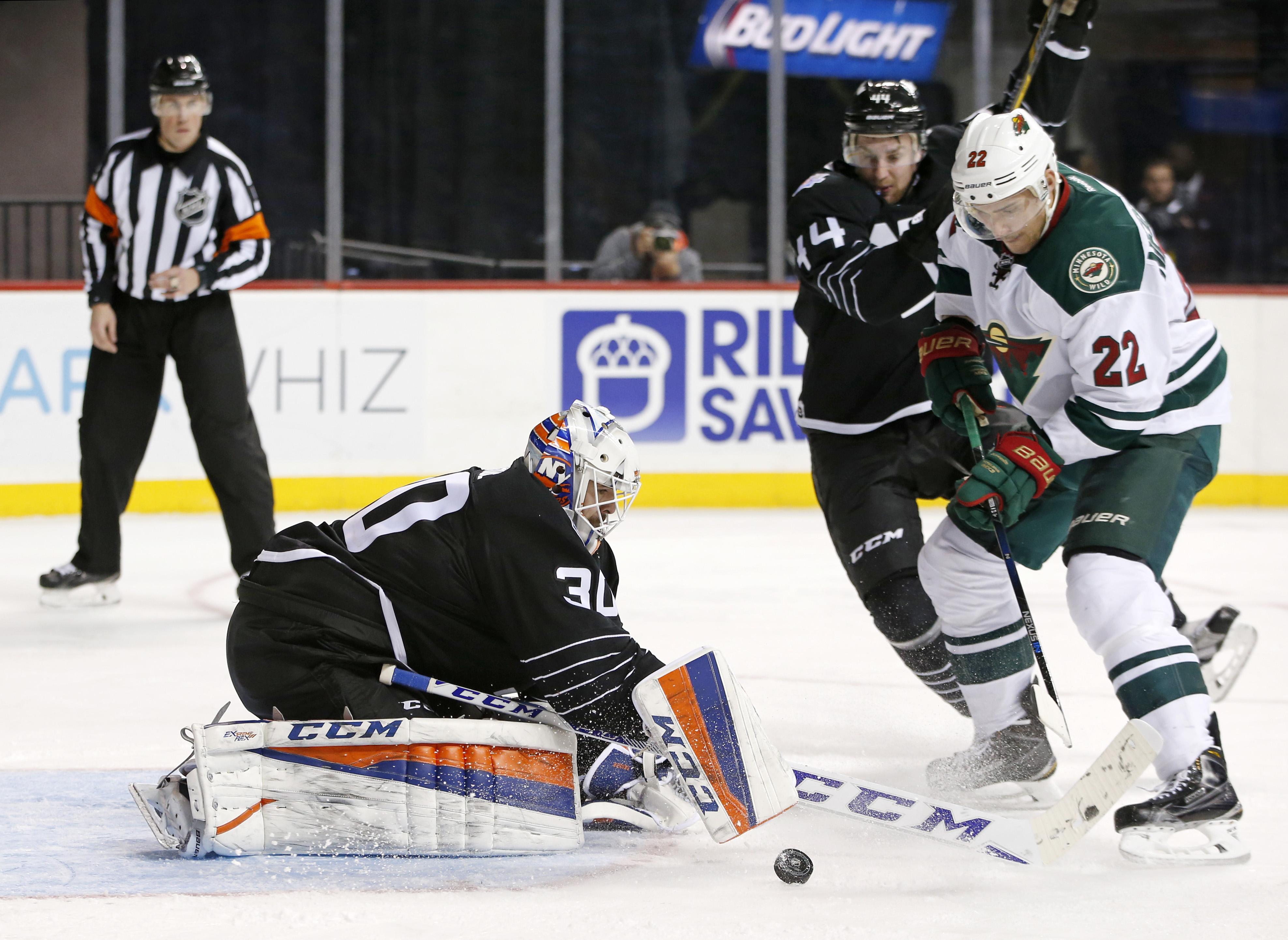 New York Islanders goalie Jean-Francois Berube (30) makes a save as defenseman Calvin de Haan (44) tries to defend Minnesota Wild right wing Nino Niederreiter (22) during the third period of an NHL hockey game in New York, Tuesday, Feb. 2, 2016. The Islan
