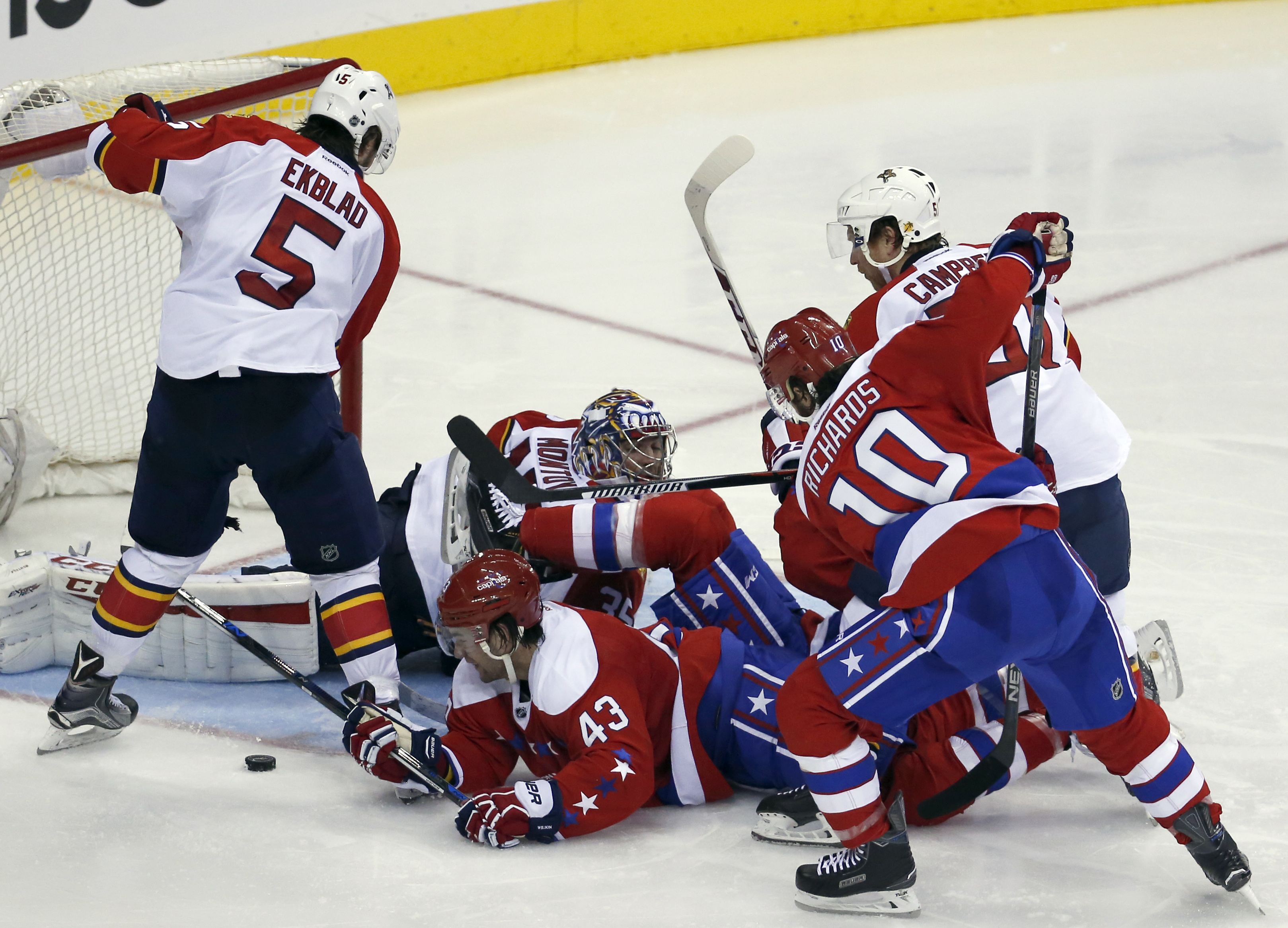 Washington Capitals right wing Tom Wilson (43) tries to play the puck lying on the ice with Florida Panthers defenseman Aaron Ekblad (5) and goalie Al Montoya (35) defending during the third period of an NHL hockey game, Tuesday, Feb. 2, 2016, in Washingt