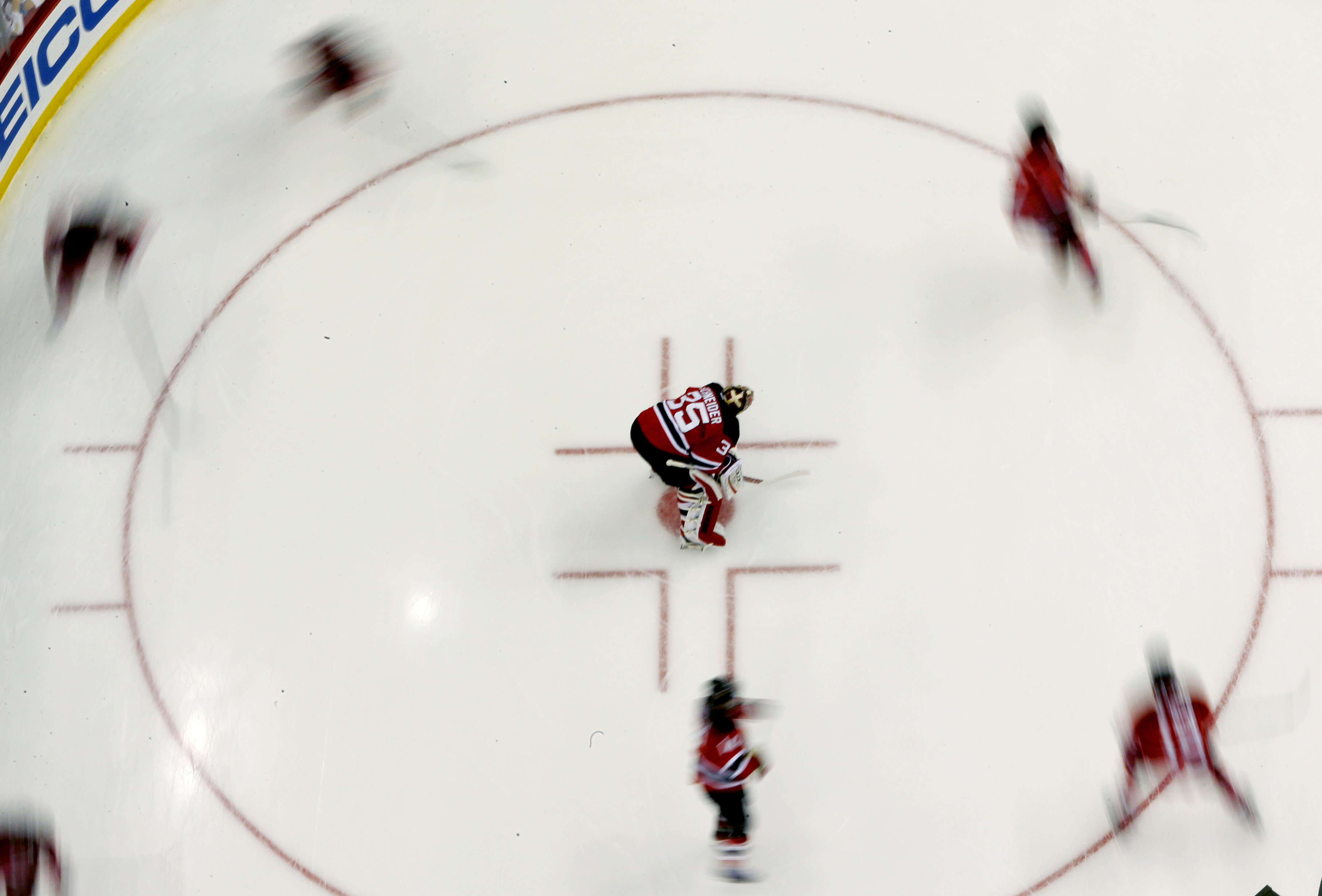 New Jersey Devils goalie Cory Schneider, center, rests while teammates skate during warmups prior to an NHL hockey game against the New York Islanders, Friday, Feb. 19, 2016, in Newark, N.J. (AP Photo/Julio Cortez)