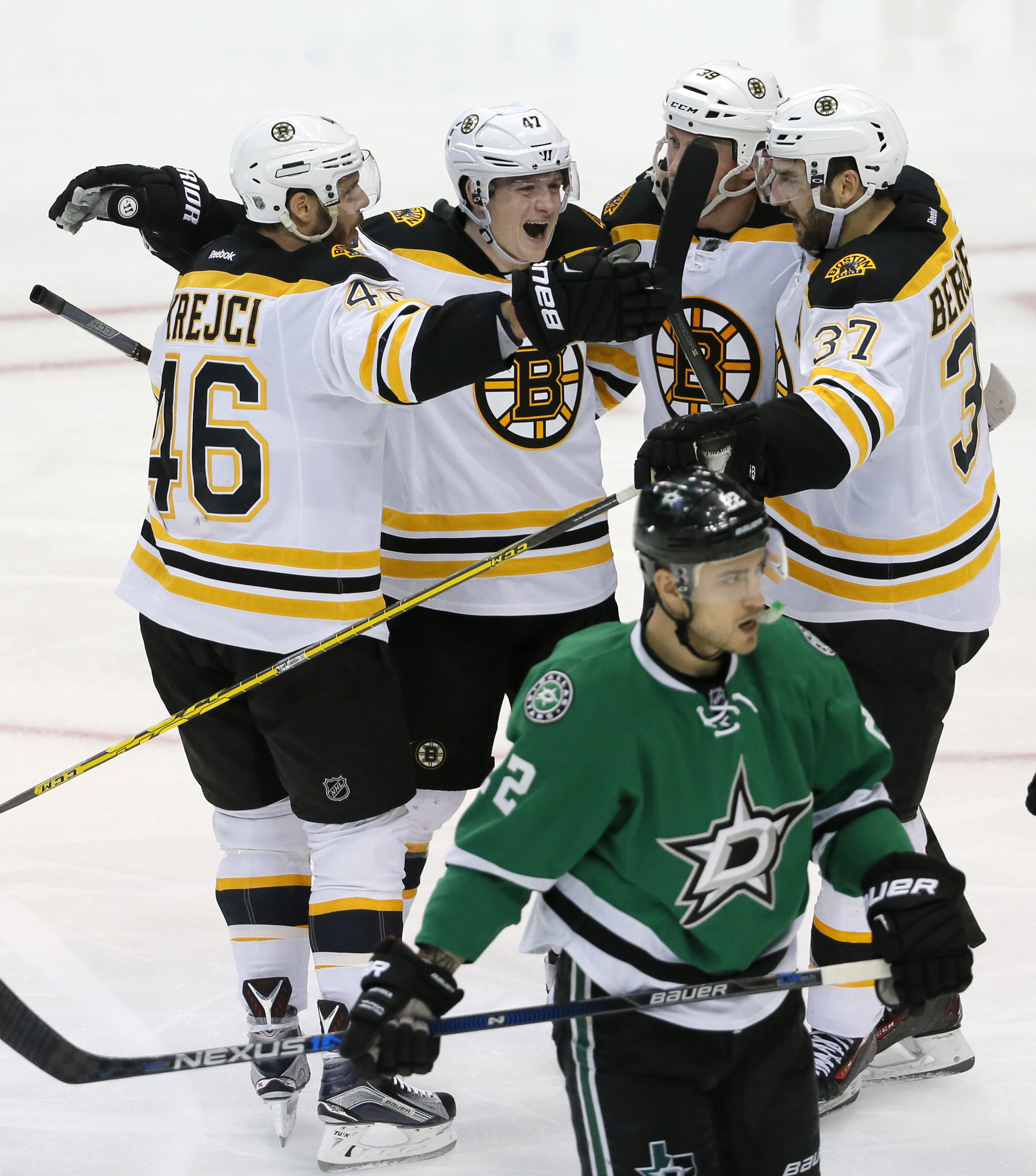 Dallas Stars' Colton Sceviour (22) skates past as Boston Bruins' David Krejci (46), of the Czech Republic, Torey Krug (47), Matt Beleskey (39) and Patrice Bergeron (37) celebrate a goal by Krejci during the third period of an NHL hockey game, Saturday, Fe