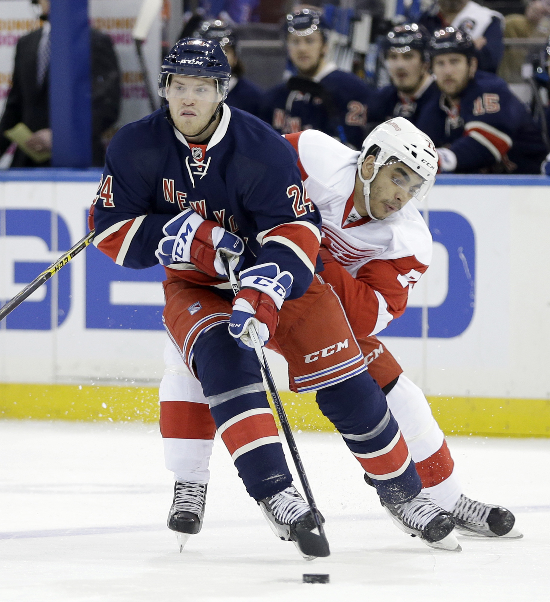 Detroit Red Wings' Andreas Athanasiou, right, tries to get the puck from New York Rangers' Oscar Lindberg during the first period of the NHL hockey game, Sunday, Feb. 21, 2016, in New York. (AP Photo/Seth Wenig)