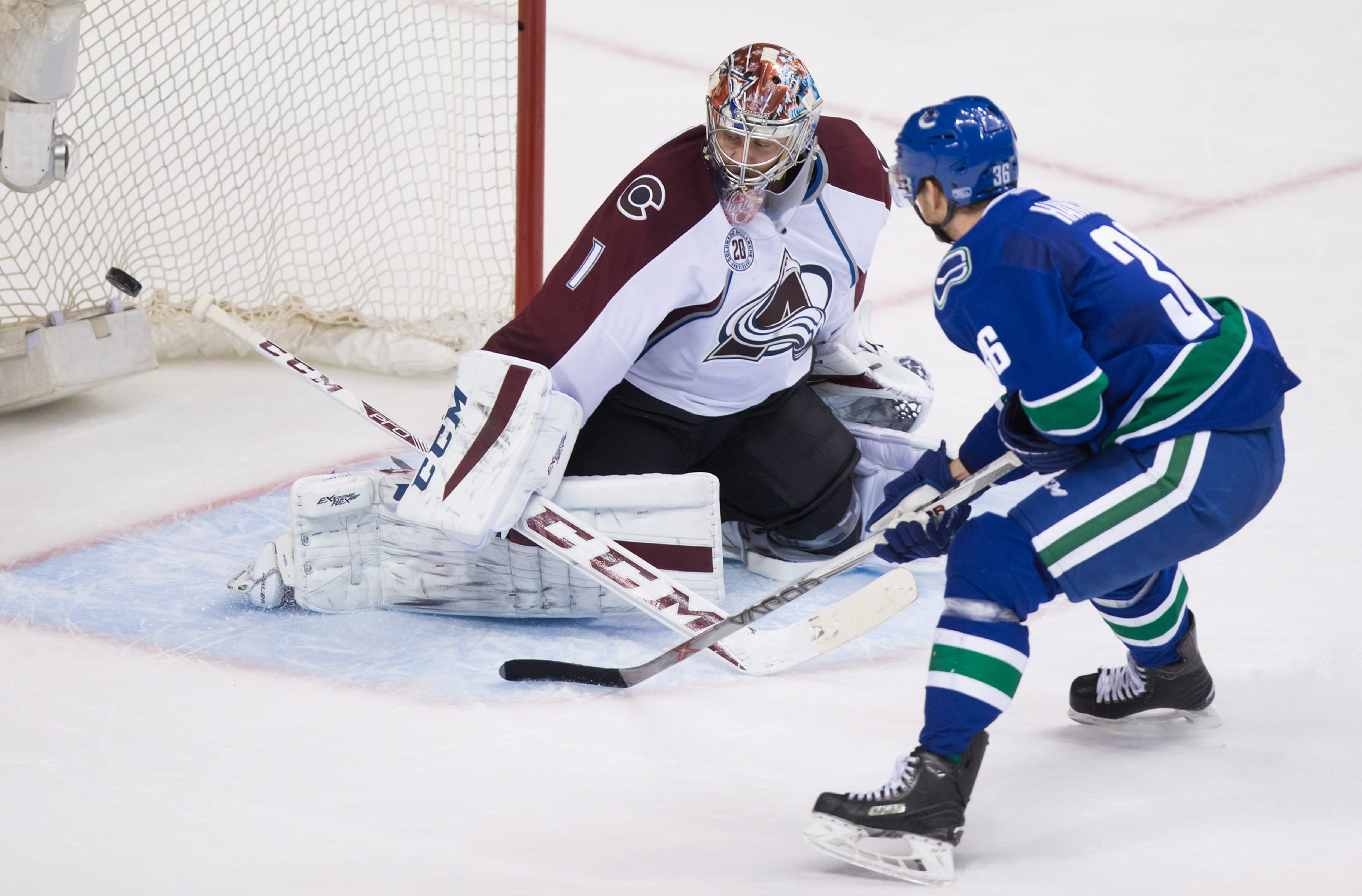 Vancouver Canucks' Jannik Hansen, right, of Denmark, scores against Colorado Avalanche goalie Semyon Varlamov, of Russia, during the third period of an NHL hockey game in Vancouver, British Columbia, Sunday, Feb. 21, 2016. (Darryl Dyck/The Canadian Press