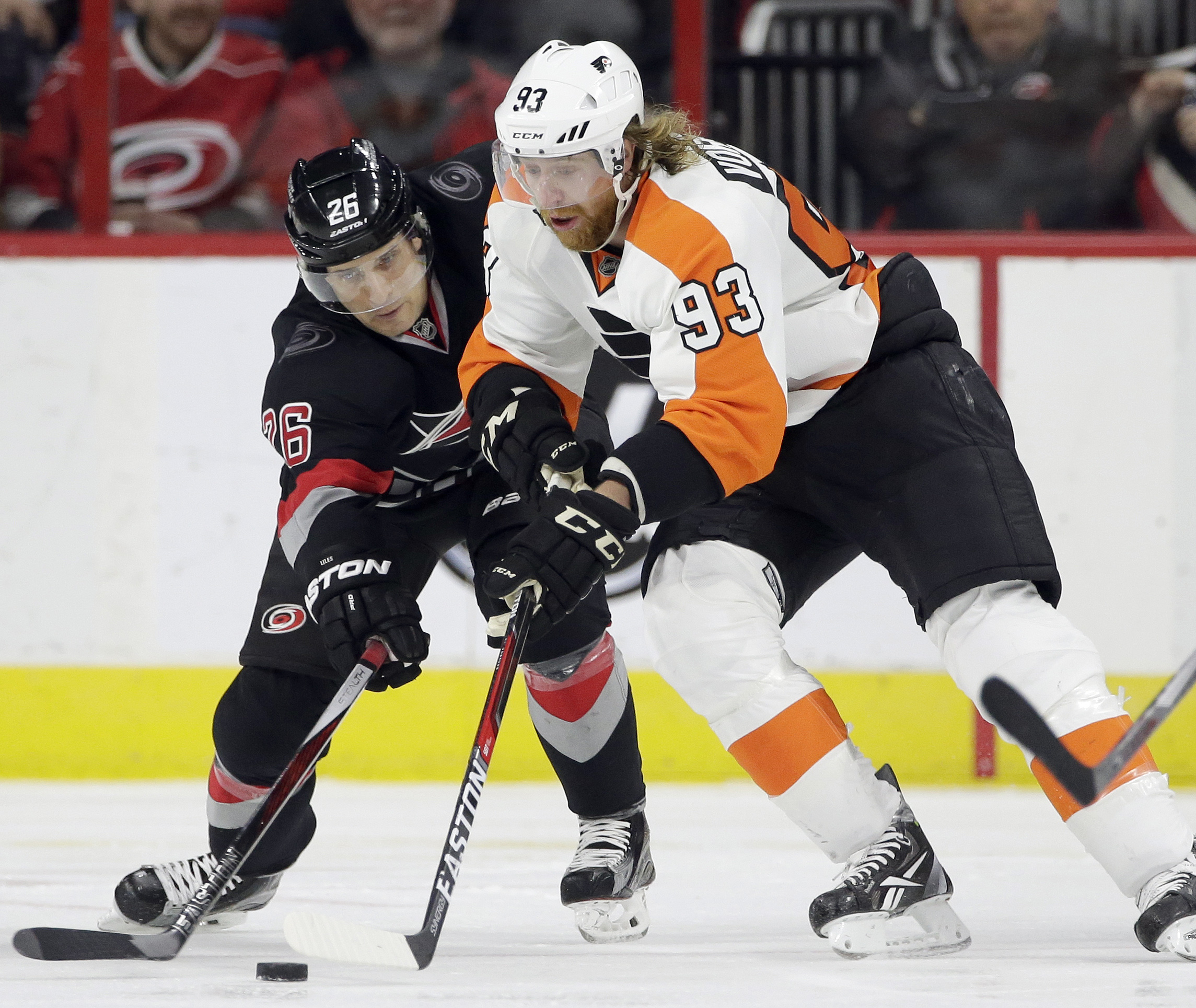 Carolina Hurricanes' John-Michael Liles (26) and Philadelphia Flyers' Jakub Voracek (93), of the Czech Republic, chase the puck during the second period of an NHL hockey game in Raleigh, N.C., Tuesday, Feb. 23, 2016. (AP Photo/Gerry Broome)