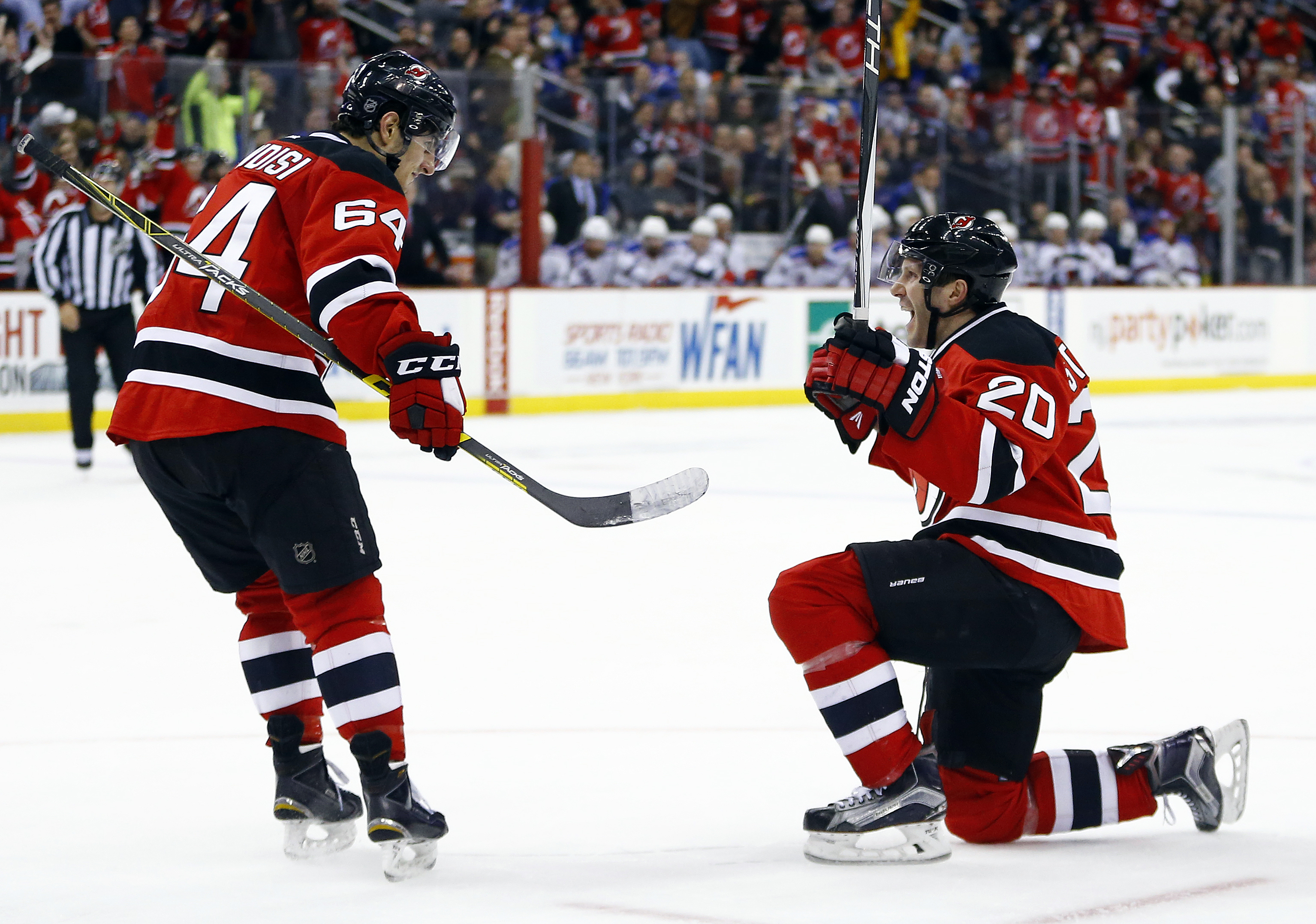 New Jersey Devils right wing Lee Stempniak (20) and center Joseph Blandisi (64) celebrate a goal by Stempniak's goal against the New York Rangers during the second period of an NHL hockey game, Tuesday, Feb. 23, 2016, in Newark, N.J. (AP Photo/Julio Corte