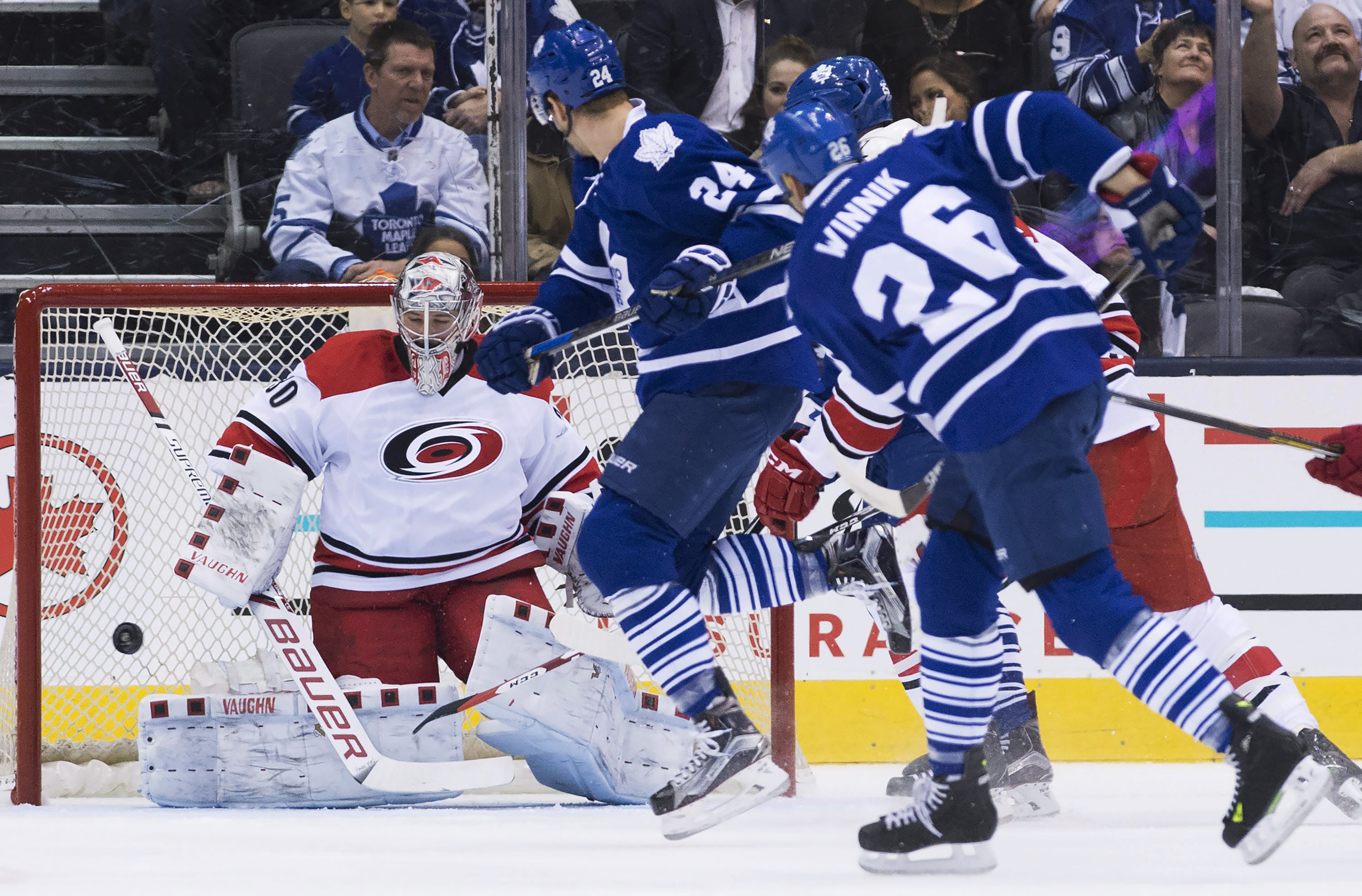 Carolina Hurricanes goalie Cam Ward (30) makes a save on Toronto Maple Leafs right wing Daniel Winnik (26) as Maple Leafs center Peter Holland (24) looks for a rebound during the first period of an NHL hockey game Thursday, Feb. 25, 2016, in Toronto. (Nat