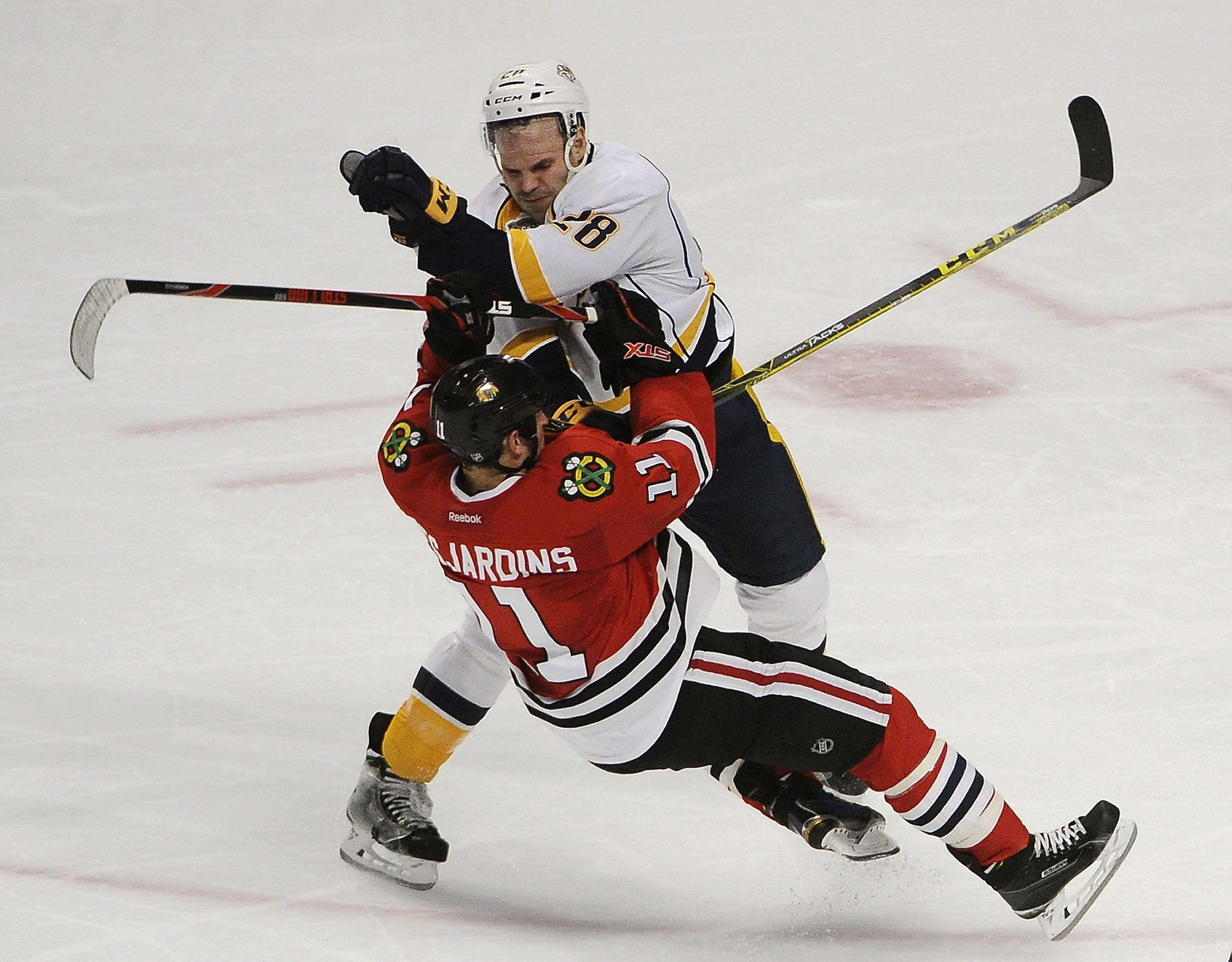 Nashville Predators center Paul Gaustad (28) checks Chicago Blackhawks center Andrew Desjardins (11) duiring the second period of an NHL hockey game Thursday, Feb. 25, 2016, in Chicago. (AP Photo/David Banks)
