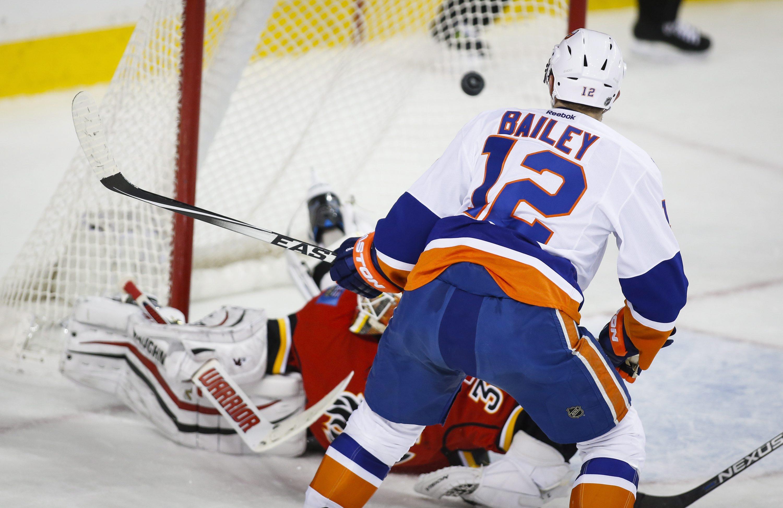 New York Islanders' Josh Bailey, right, scores the winning goal on Calgary Flames goalie Joni Ortio, from Finland, during overtime NHL hockey action in Calgary, Alberta, Thursday, Feb. 25, 2016. (Jeff McIntosh/The Canadian Press via AP) MANDATORY CREDIT