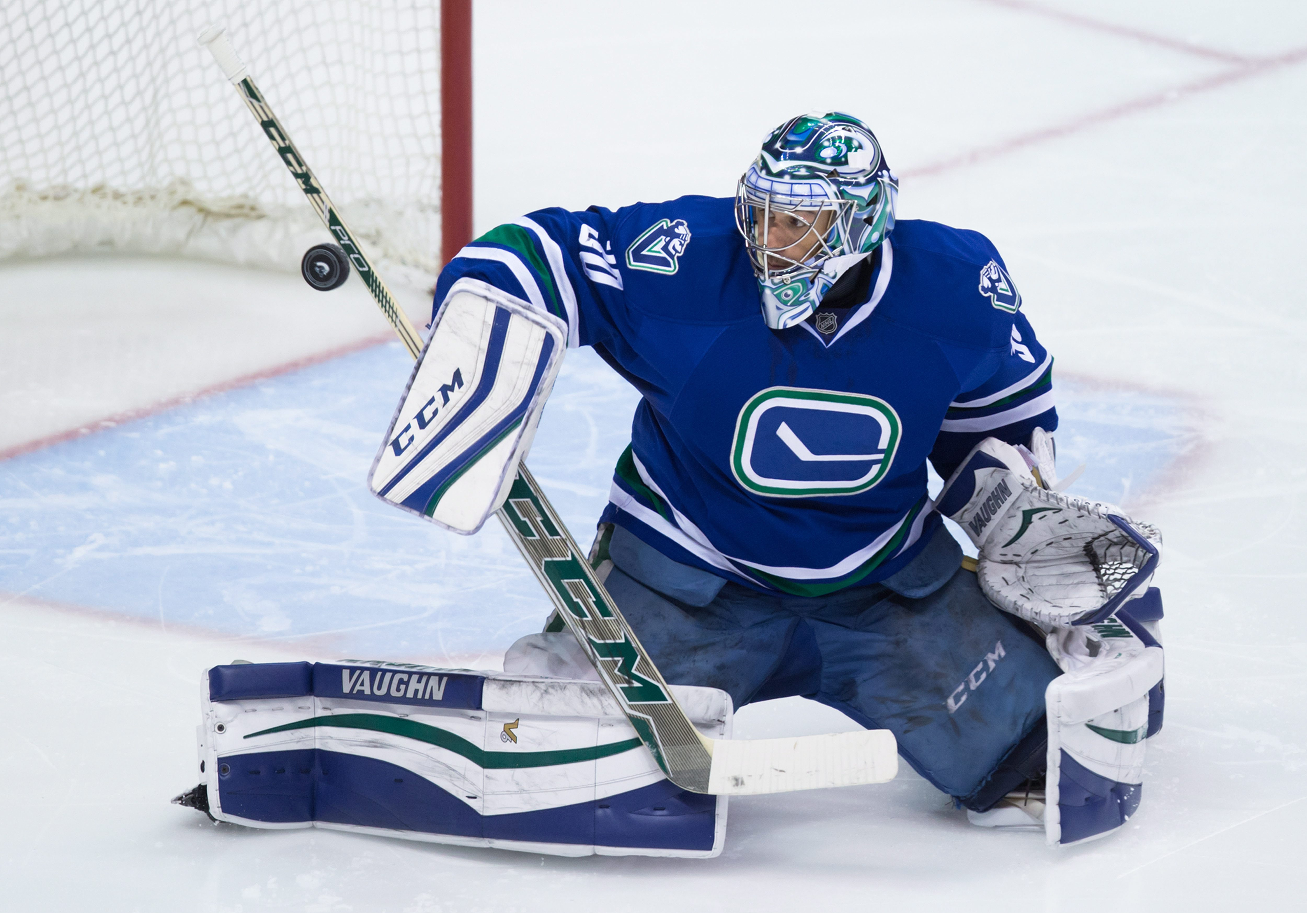Vancouver Canucks goalie Ryan Miller makes a blocker save against the Ottawa Senators during the second period of an NHL hockey game Thursday, Feb. 25, 2016, in Vancouver, British Columbia. (Darryl Dyck/The Canadian Press via AP)