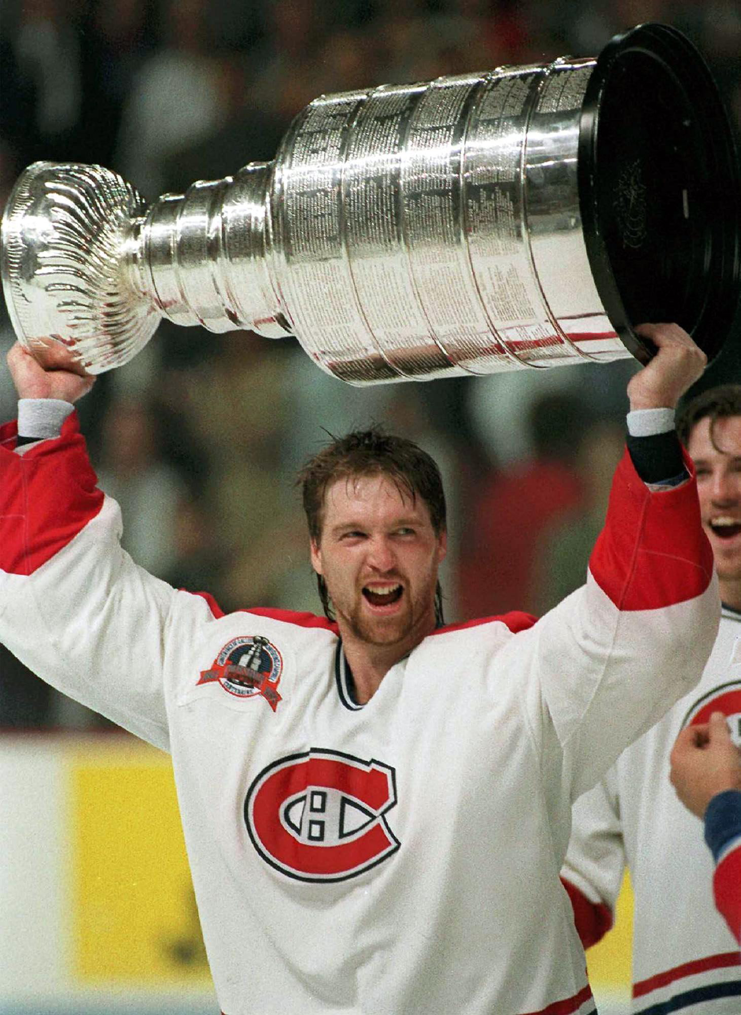 FILE - In this June 9, 1993,  file photo, Montreal Canadiens goalie Patrick Roy hoists the Stanley Cup Trophy after the Canadiens defeated the Los Angeles Kings to win the Stanley Cup, in Montreal. Roy was a talented tennis player and swimmer, one of the