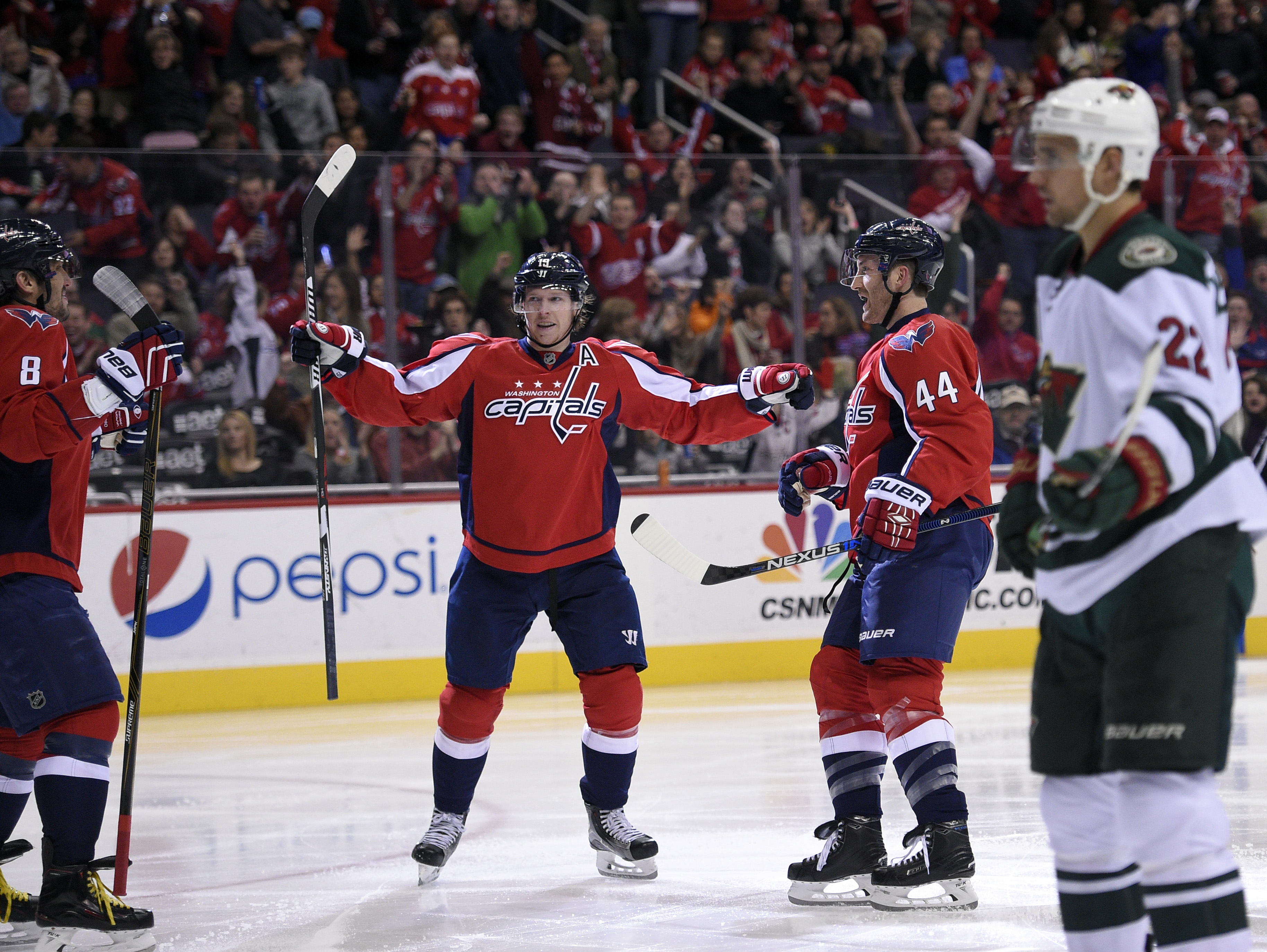 Washington Capitals defenseman Brooks Orpik (44) celebrates his goal with center Nicklas Backstrom (19), of Sweden, and left wing Alex Ovechkin (8), of Russia, during the second period of an NHL hockey game, as Minnesota Wild right wing Nino Niederreiter