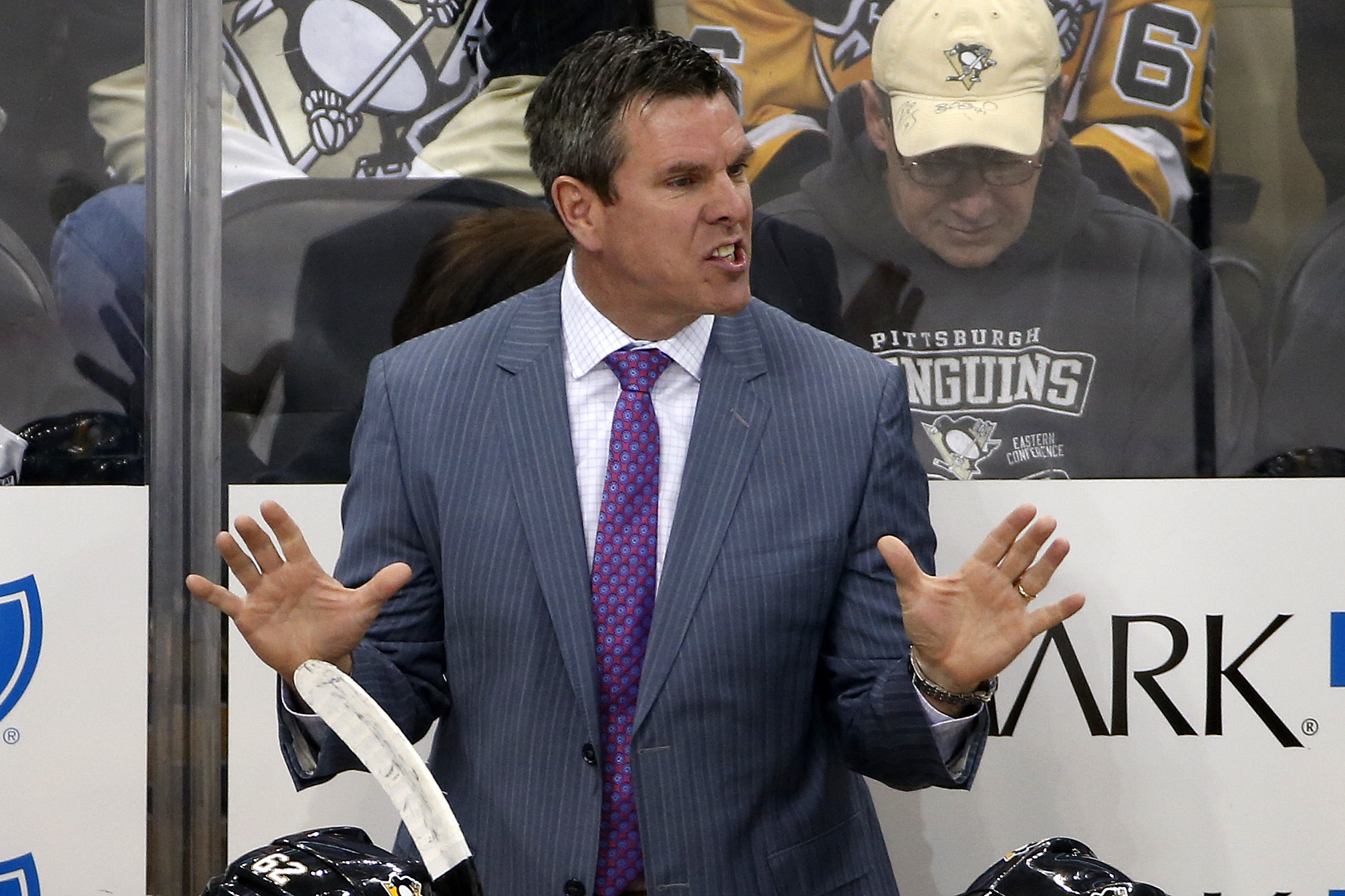 Pittsburgh Penguins head coach Mike Sullivan talks with a linesman during the first period of an NHL hockey game against the Winnipeg Jets in Pittsburgh, Saturday, Feb. 27, 2016. The Penguins won 4-1. (AP Photo/Gene J. Puskar)