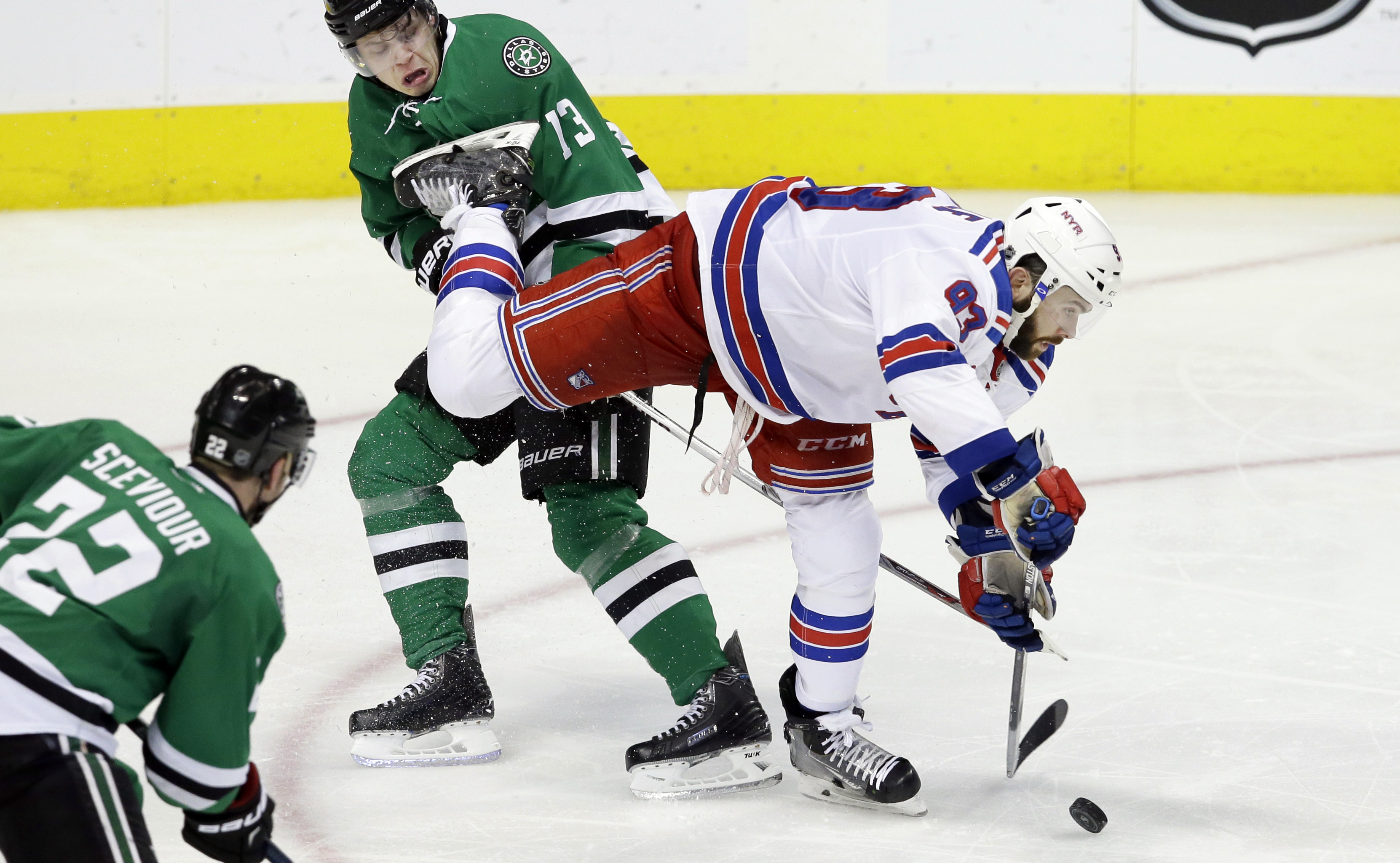 New York Rangers defenseman Keith Yandle (93) reaches for the puck against Dallas Stars center Mattias Janmark (13) as Stars' Colton Sceviour (22) looks on during the third period of an NHL hockey game Saturday, Feb. 27, 2016, in Dallas. The Rangers won 3