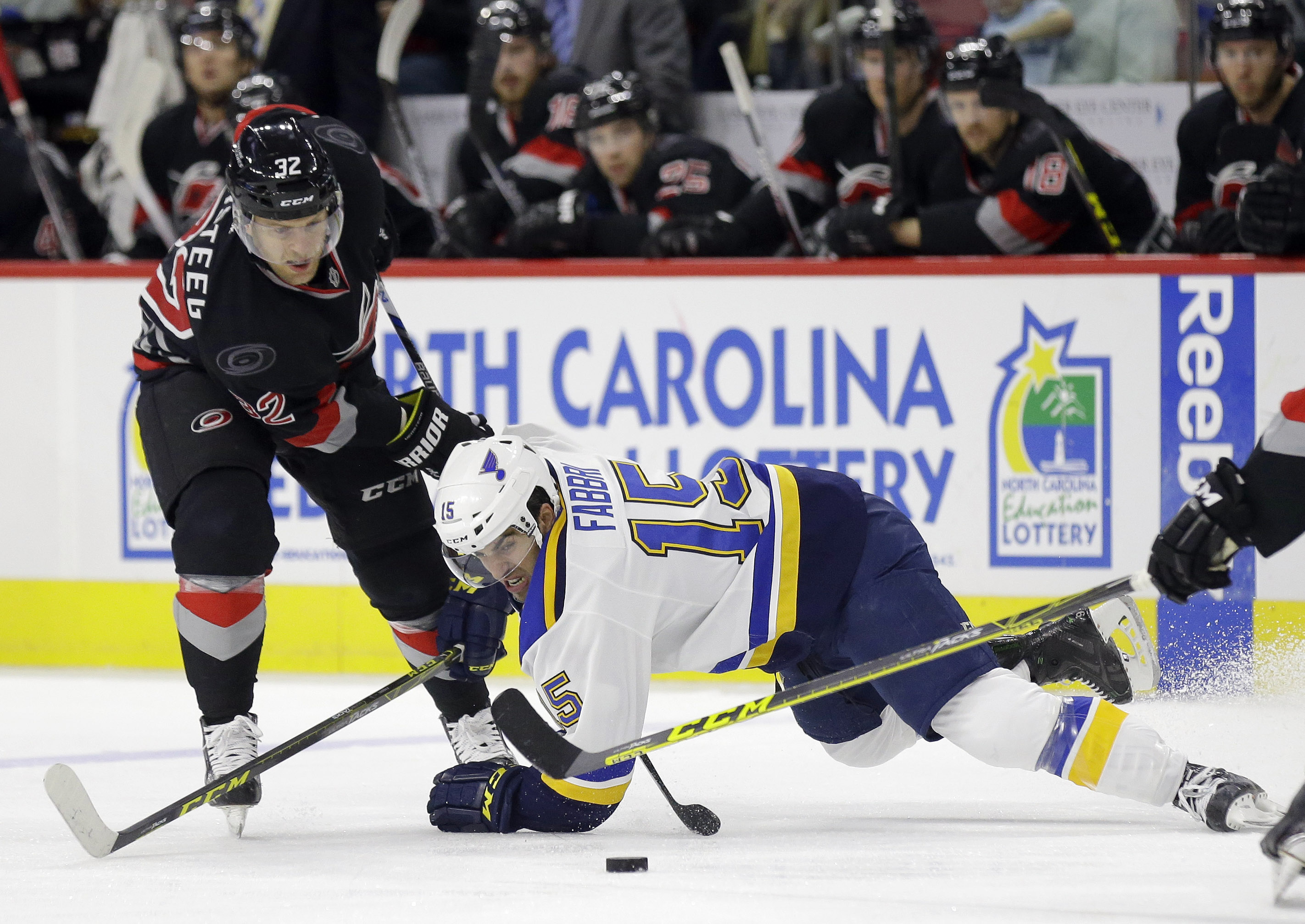 St. Louis Blues' Robby Fabbri (15) falls while chasing the puck with Carolina Hurricanes' Kris Versteeg (32) during the first period of an NHL hockey game in Raleigh, N.C., Sunday, Feb. 28, 2016. (AP Photo/Gerry Broome)