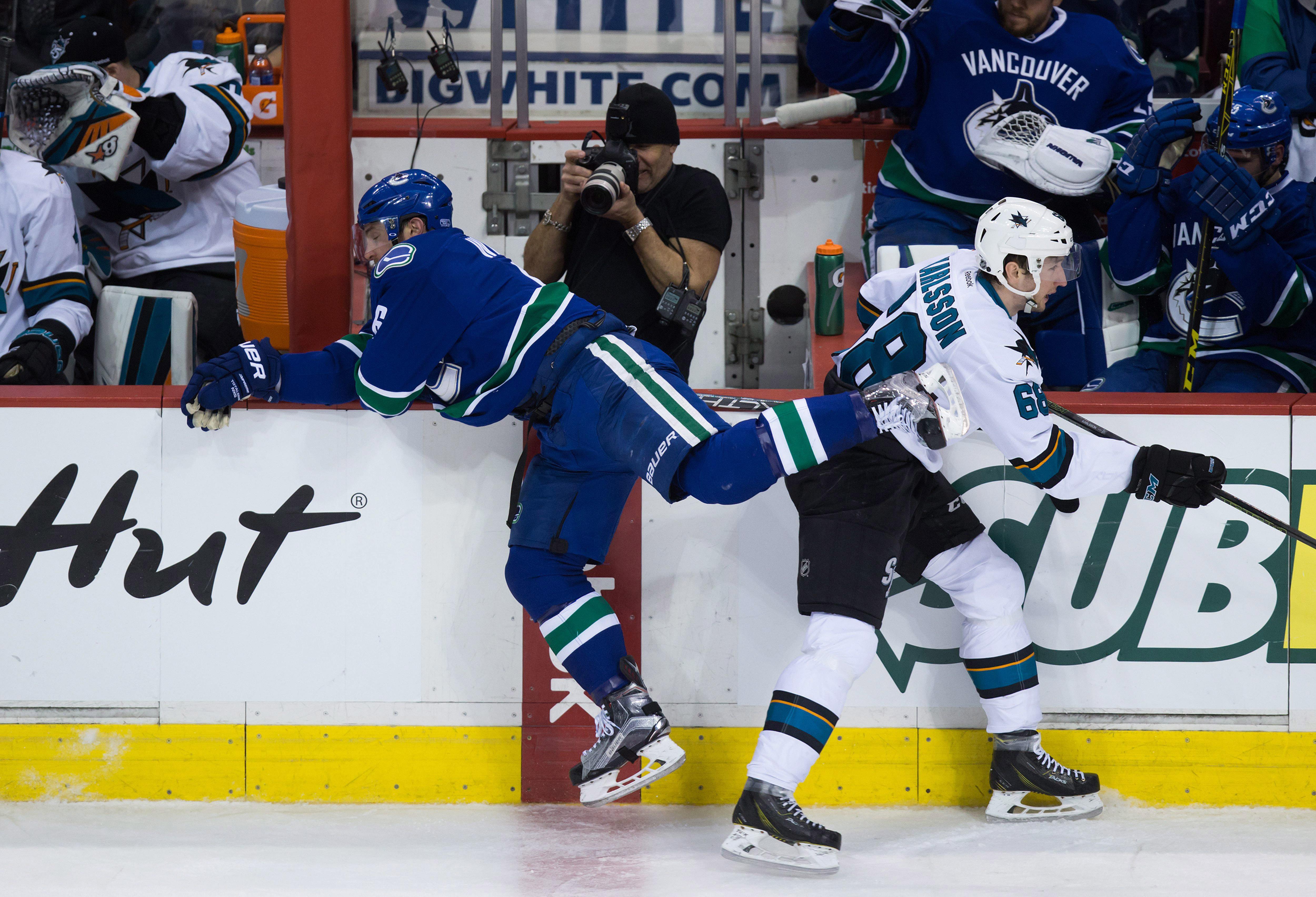Vancouver Canucks' Yannick Weber, left, of Switzerland, and San Jose Sharks' Melker Karlsson, of Sweden, collide during second period NHL hockey action in Vancouver on Sunday, Feb. 28, 2016. (Darryl Dyck/The Canadian Press via AP) MANDATORY CREDIT