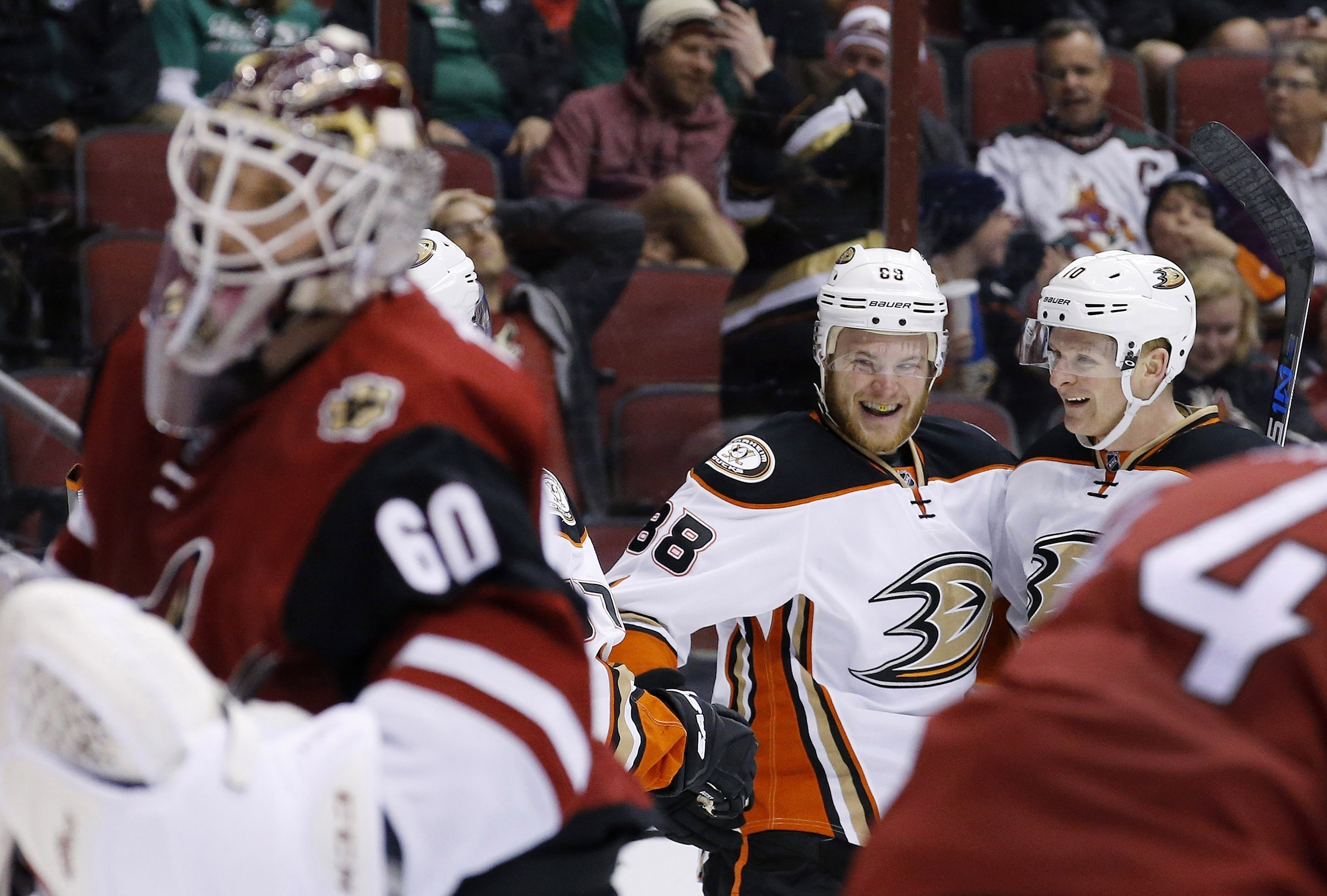 Anaheim Ducks' Jamie McGinn (88) smiles as he celebrates his goal against Arizona Coyotes' Niklas Treutle (60), of Germany, with teammate Corey Perry (10) during the first period of an NHL hockey game Thursday, March 3, 2016, in Glendale, Ariz. (AP Photo/