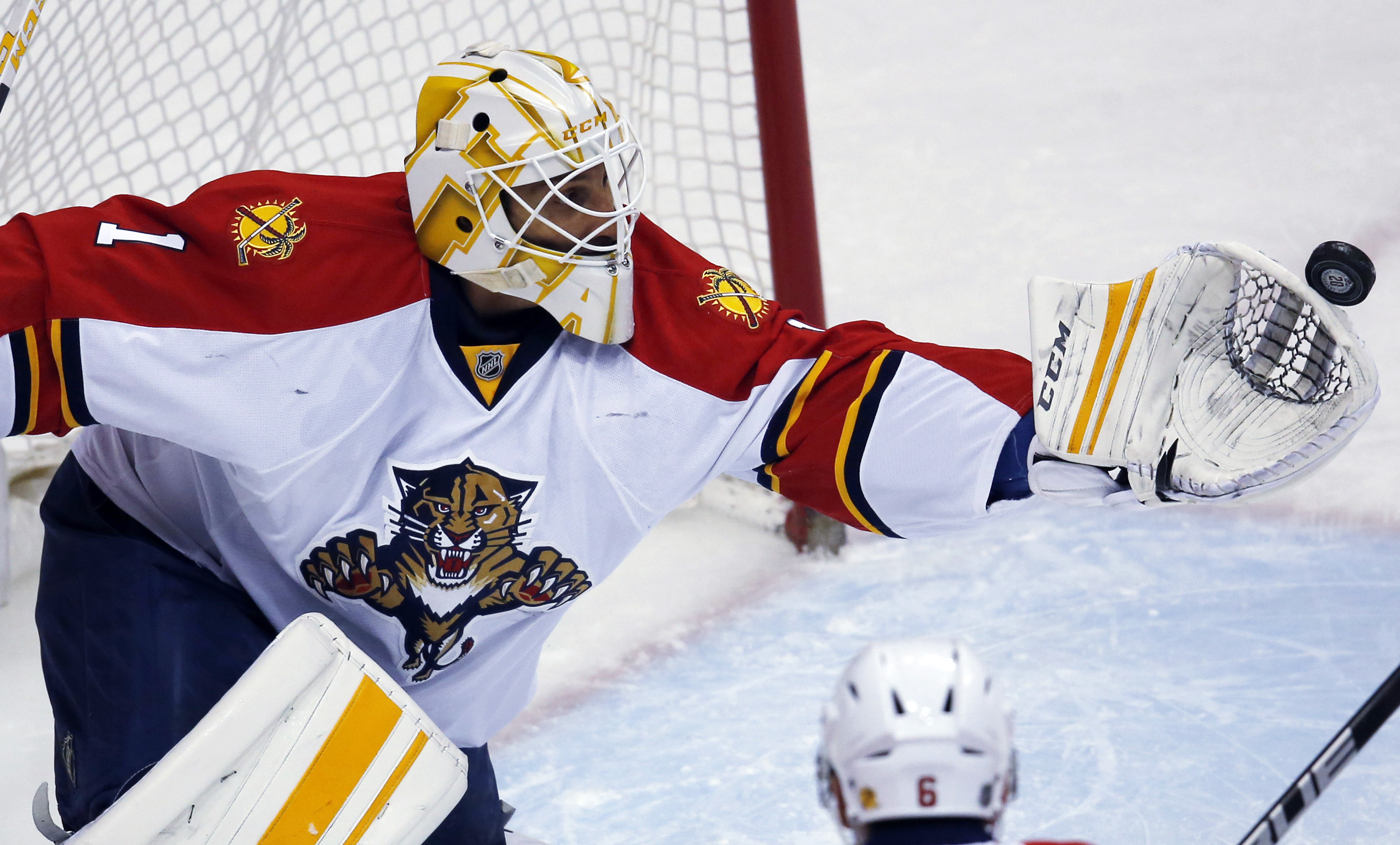 Florida Panthers goalie Roberto Luongo reaches out to stop a shot in the first period of an NHL hockey game against the Colorado Avalanche, Thursday, March 3, 2016, in Denver. (AP Photo/David Zalubowski)
