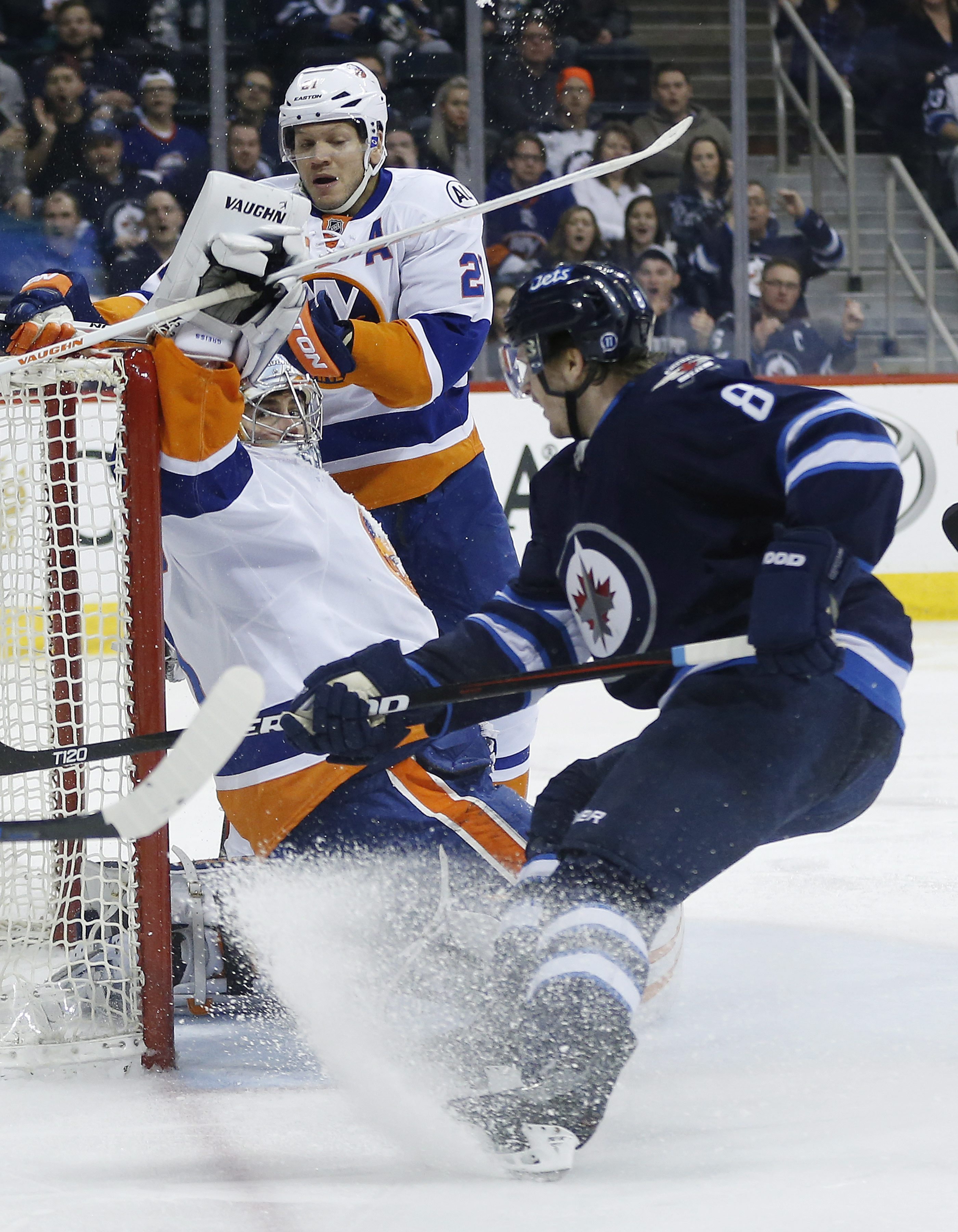New York Islanders goaltender Thomas Greiss (1) keeps his eye on the puck sitting on his blocker as Winnipeg Jets' Jacob Trouba (8) hopes for a rebound and Islanders' Kyle Okposo (21) defends during second-period NHL hockey game action in Winnipeg, Manito