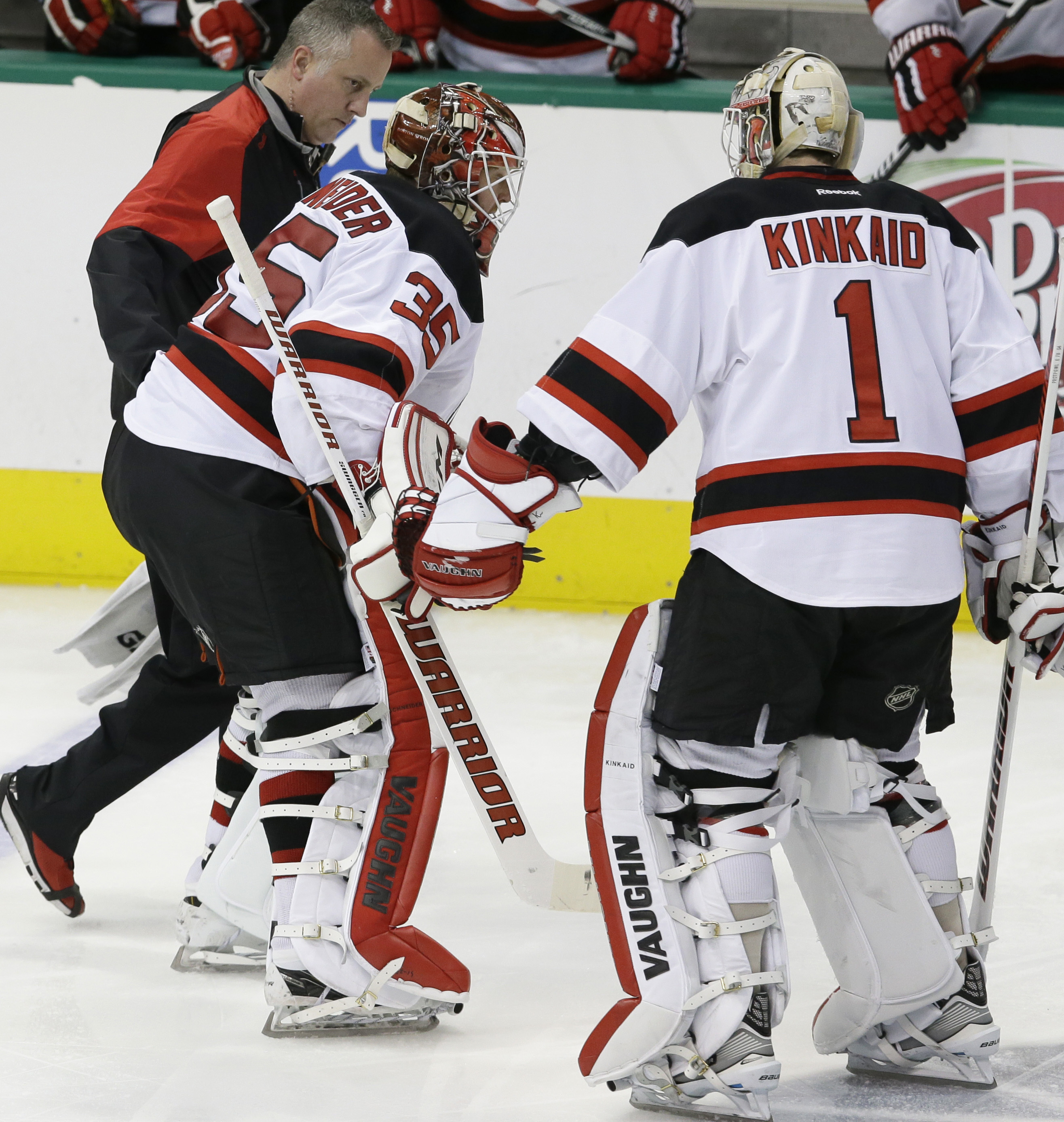 New Jersey Devils goalie Cory Schneider (35) leaves the game with an injury as fellow goalie Keith Kinkaid (1) come in to play during the third period of an NHL hockey game against the Dallas Stars Friday, March 4, 2016, in Dallas. The Stars won 4-2. (AP