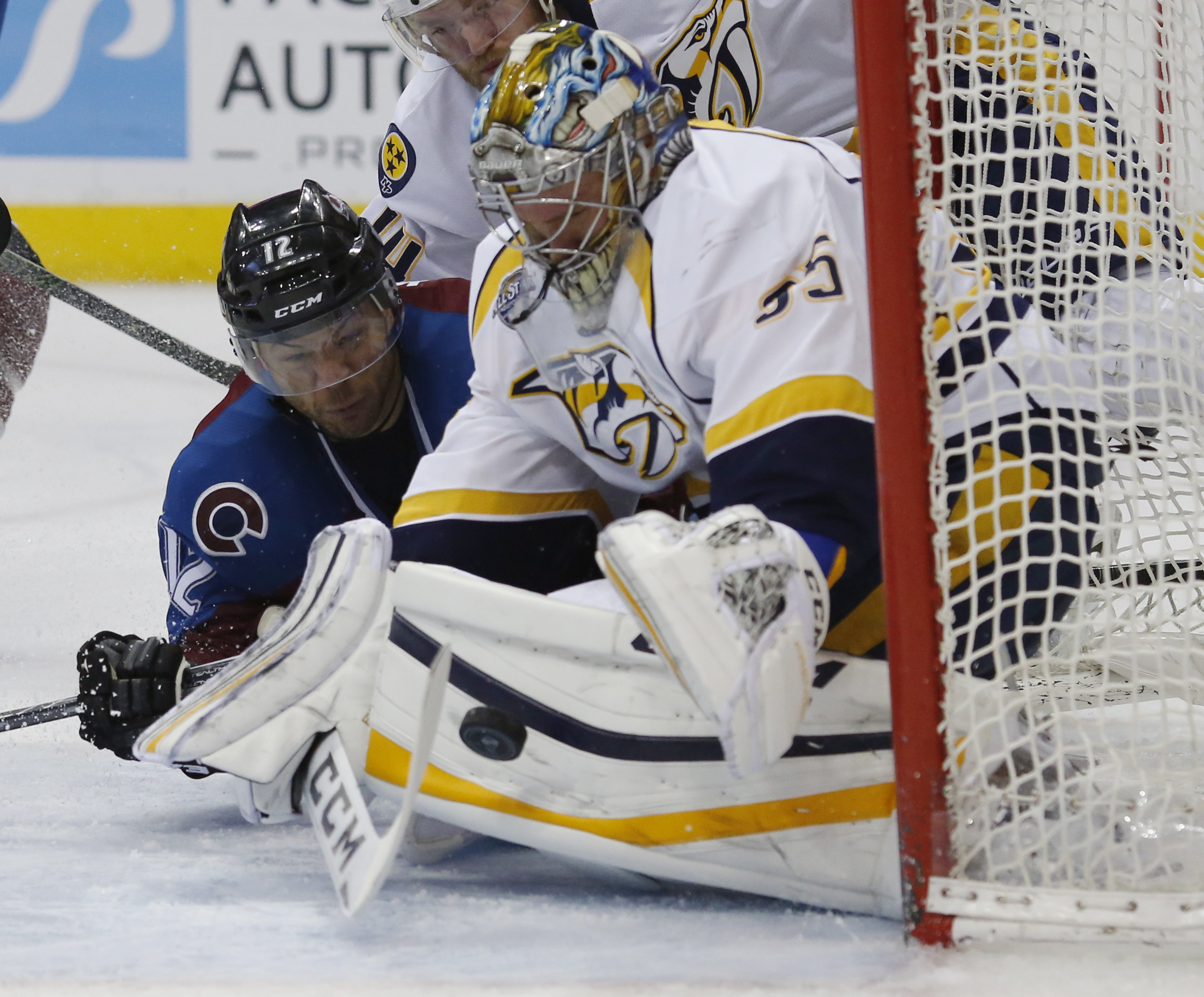 Nashville Predators goalie Pekka Rinne, front, of Finland, reaches out to stop a shot off the stick of Colorado Avalanche right wing Jarome Iginla in the third period of an NHL hockey game Saturday, March 5, 2016, in Denver. Nashville won 5-2. (AP Photo/D