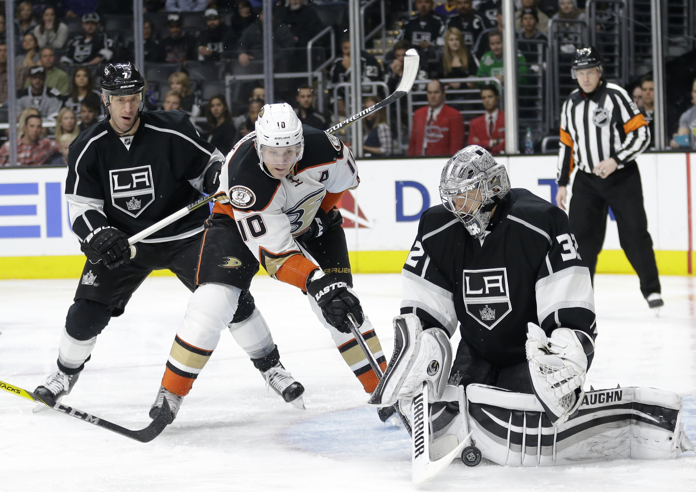 Los Angeles Kings goalie Jonathan Quick, front right, stops a shot by Anaheim Ducks' Corey Perry as Kings' Rob Scuderi, left, watches during the third period of an NHL hockey game, Saturday, March 5, 2016, in Los Angeles. (AP Photo/Jae C. Hong)