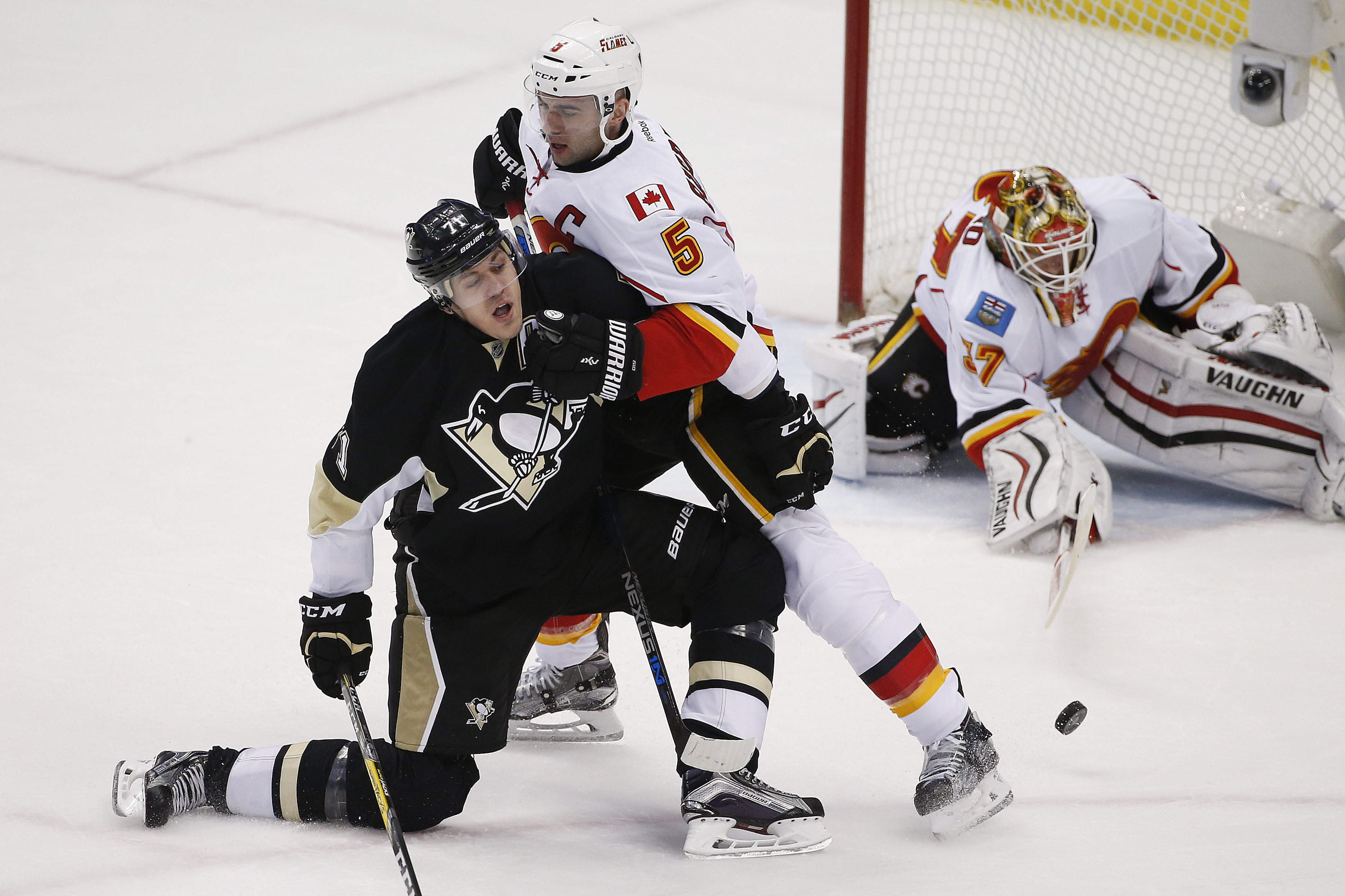 Pittsburgh Penguins' Evgeni Malkin (71) is knocked off the puck by Calgary Flames' Mark Giordano (5) in front of goalie Joni Ortio (37) during the first period of an NHL hockey game in Pittsburgh, Saturday, March 5, 2016. (AP Photo/Gene J. Puskar)