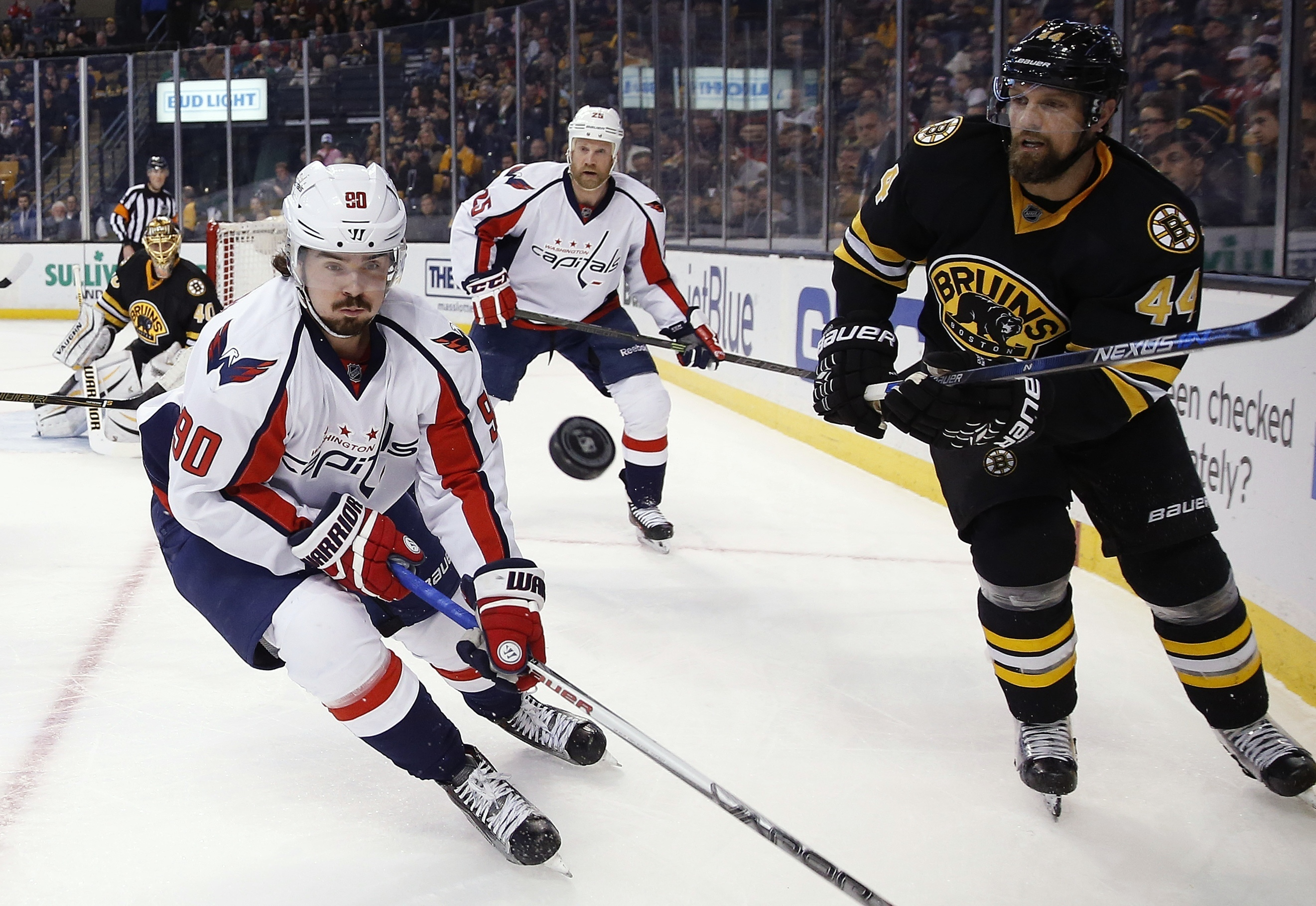 Boston Bruins' Dennis Seidenberg (44) sends the puck past Washington Capitals' Marcus Johansson (90) during the first period of an NHL hockey game in Boston, Saturday, March 5, 2016. (AP Photo/Michael Dwyer)