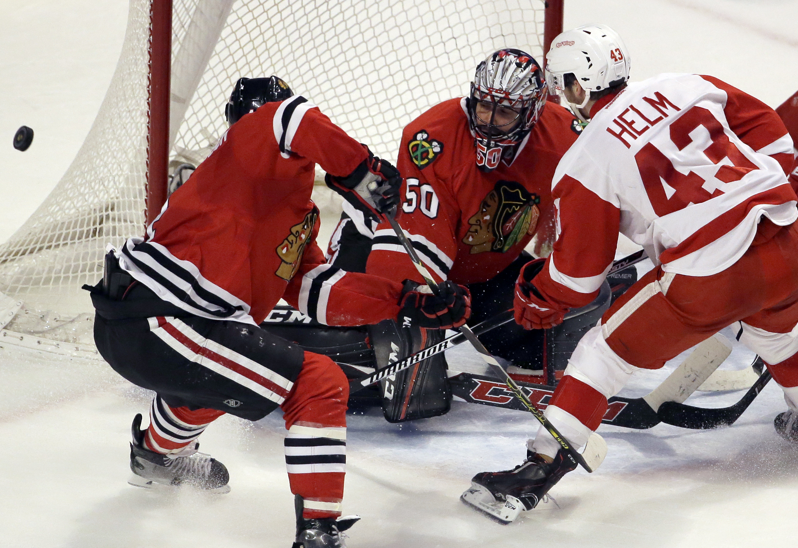 Chicago Blackhawks goalie Corey Crawford (50) blocks a shot by Detroit Red Wings center Darren Helm during the second period of an NHL hockey game Sunday, March 6, 2016, in Chicago. (AP Photo/Nam Y. Huh)