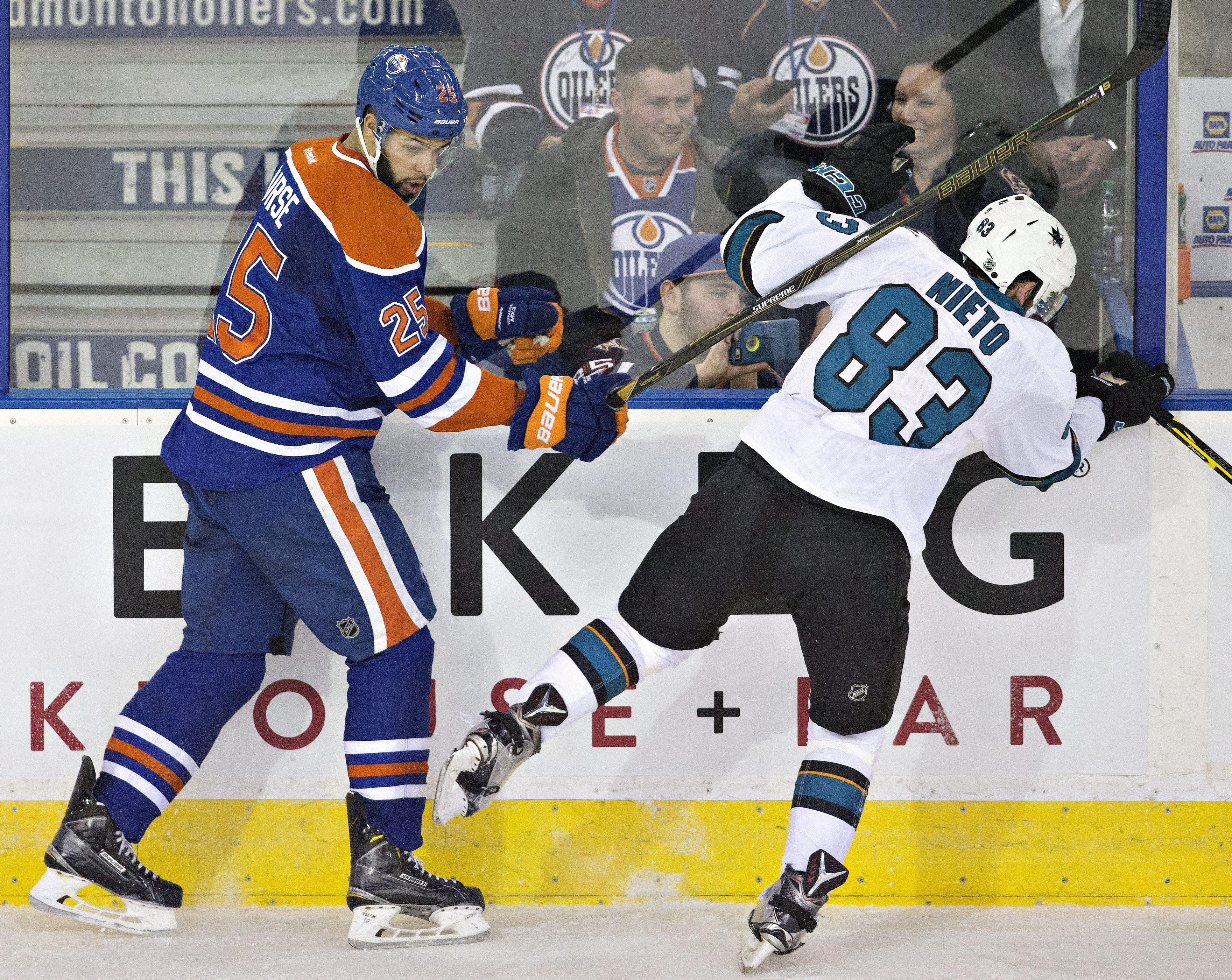 San Jose Sharks ' Matt Nieto (83) is checked by Edmonton Oilers' Darnell Nurse (25) during second period NHL action in Edmonton, Alberta, Tuesday March 8, 2016. (Jason Franson/The Canadian Press via AP)