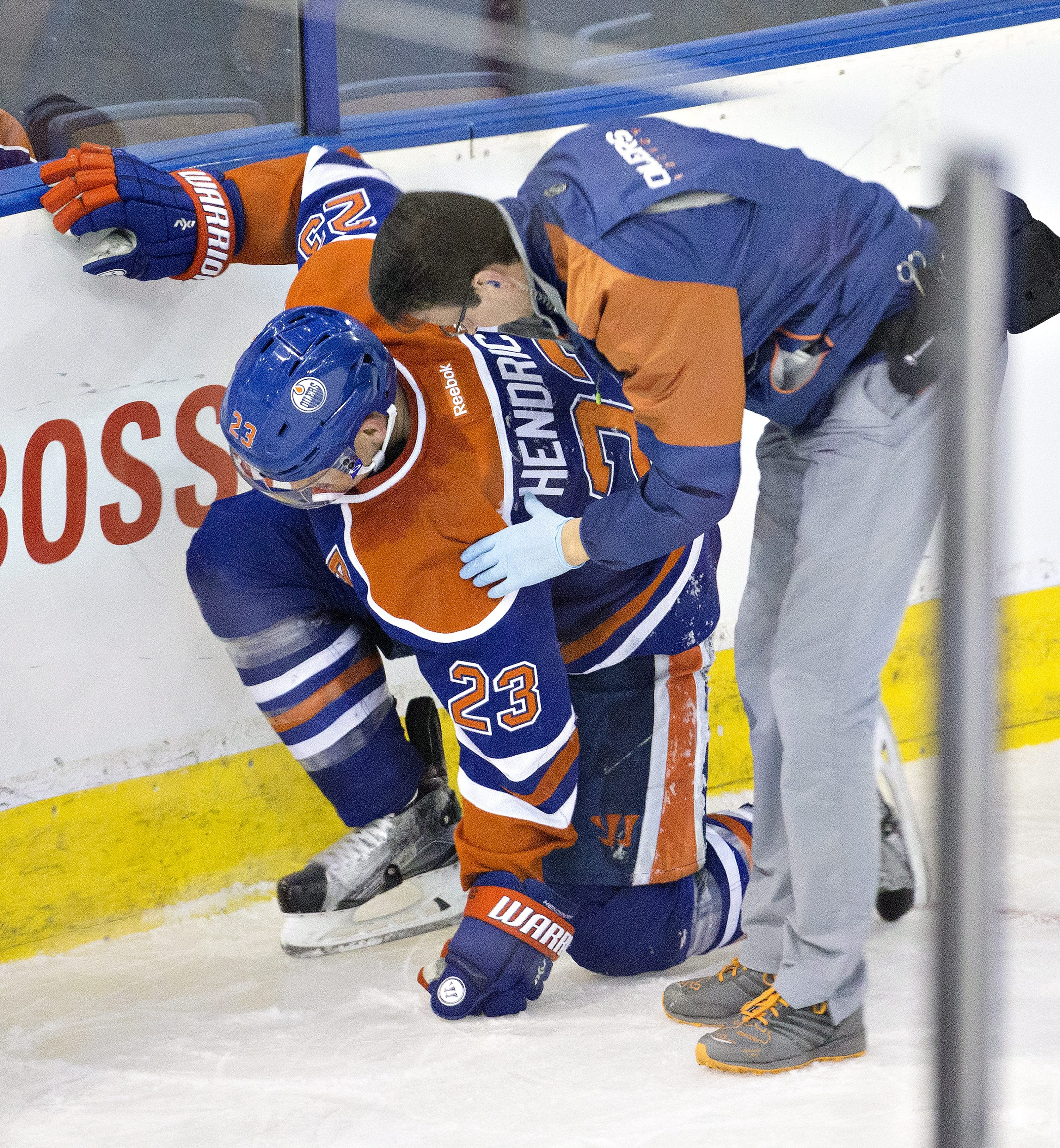 A trainer attends to Edmonton Oilers' Matt Hendricks (23) ad he tries to get up after a check from the San Jose Sharks during third period NHL action in Edmonton, Alberta, Tuesday March 8, 2016. (Jason Franson/The Canadian Press via AP)