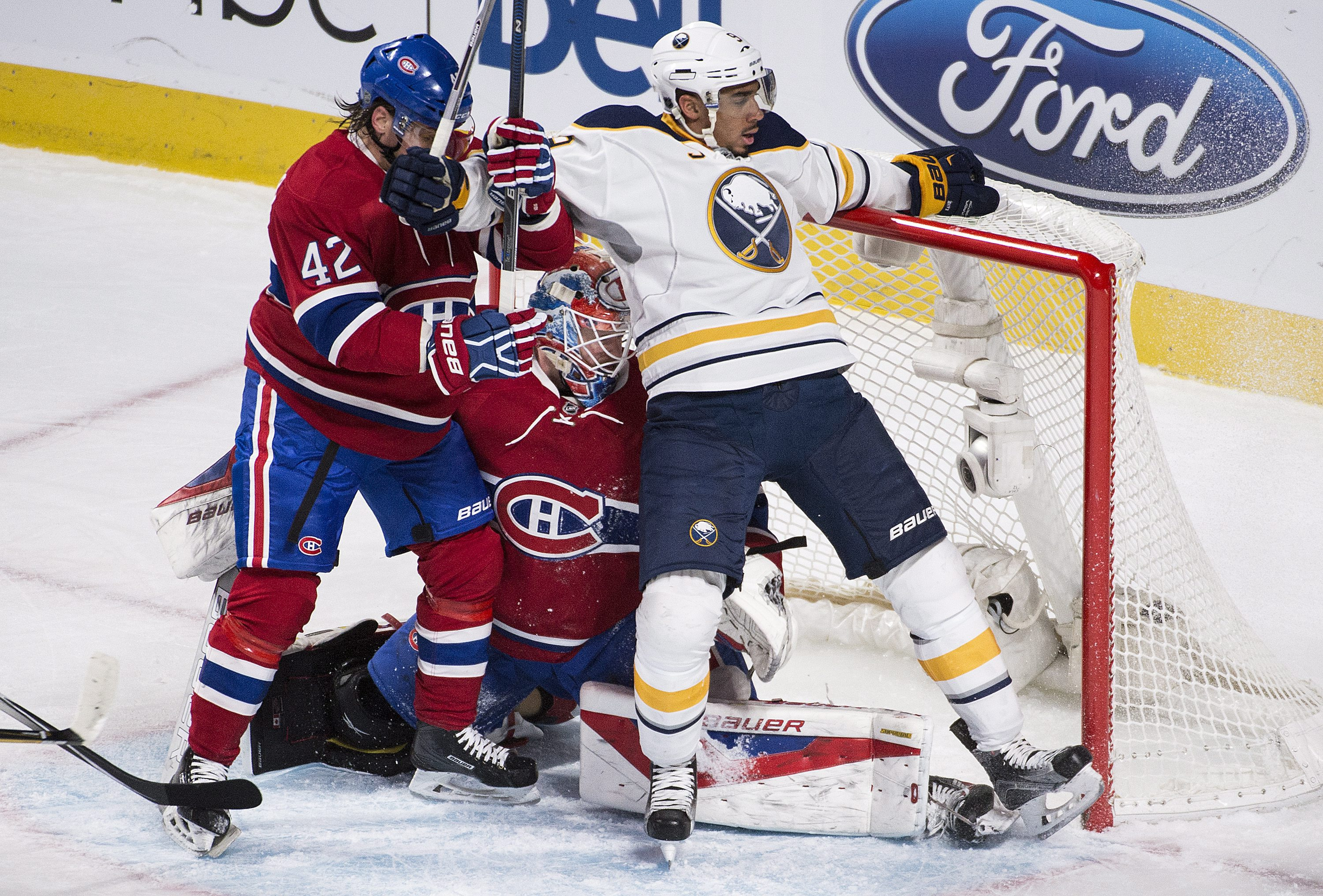 Buffalo Sabres' Evander Kane, right, collides with Montreal Canadiens goaltender Mike Condon as Canadiens' Sven Andrighetto (42) defends during the first period of an NHL hockey game Thursday, March 10, 2016, in Montreal. (Graham Hughes/The Canadian Press