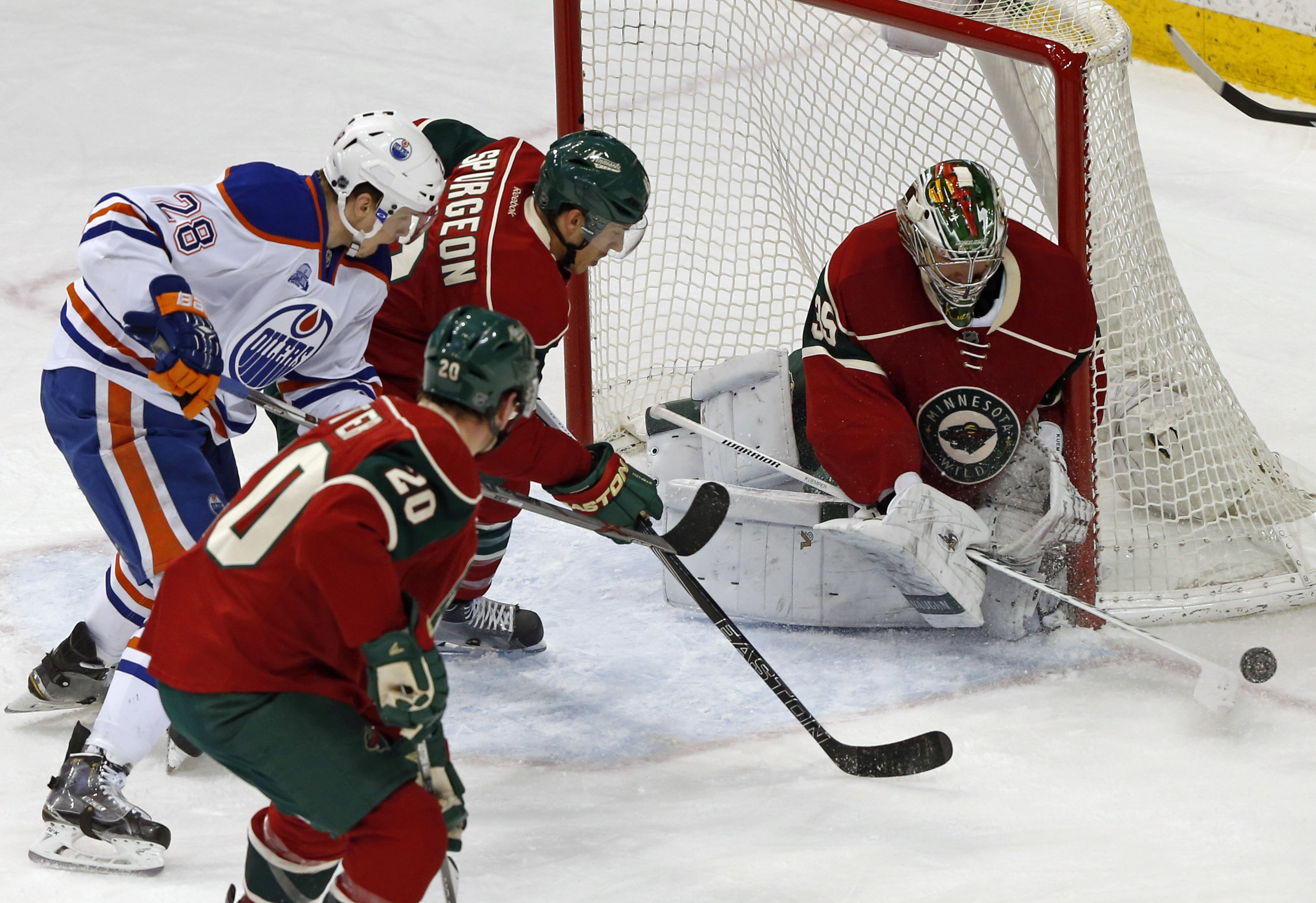 Minnesota Wild goalie Darcy Kuemper, right, blocks a shot as Edmonton Oilers' Lauri Korpikoski, left, of Finland, is caught between Wilds Ryan Suter (20) and Jared Spurgeon in the first period of an NHL hockey game Thursday, March 10, 2016, in St. Paul, M