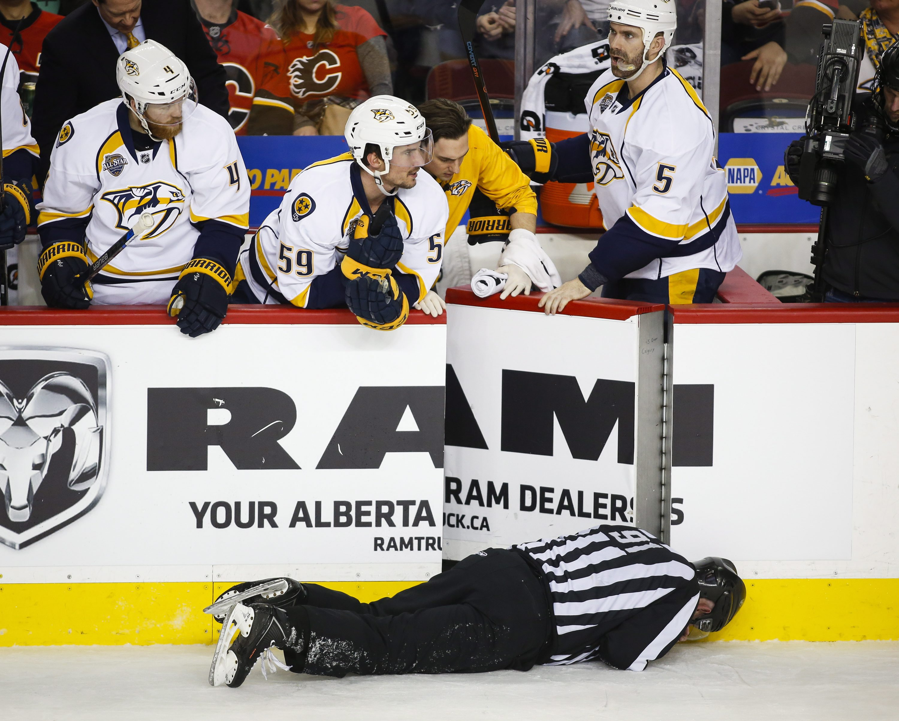 FILE - This Jan. 27, 2016 file photo shows Nashville Predators' players looking over the bench at linesman Don Henderson after he was hit by Calgary Flames' Dennis Wideman during second period NHL hockey action in Calgary, Alberta. Wideman's 20-game suspe
