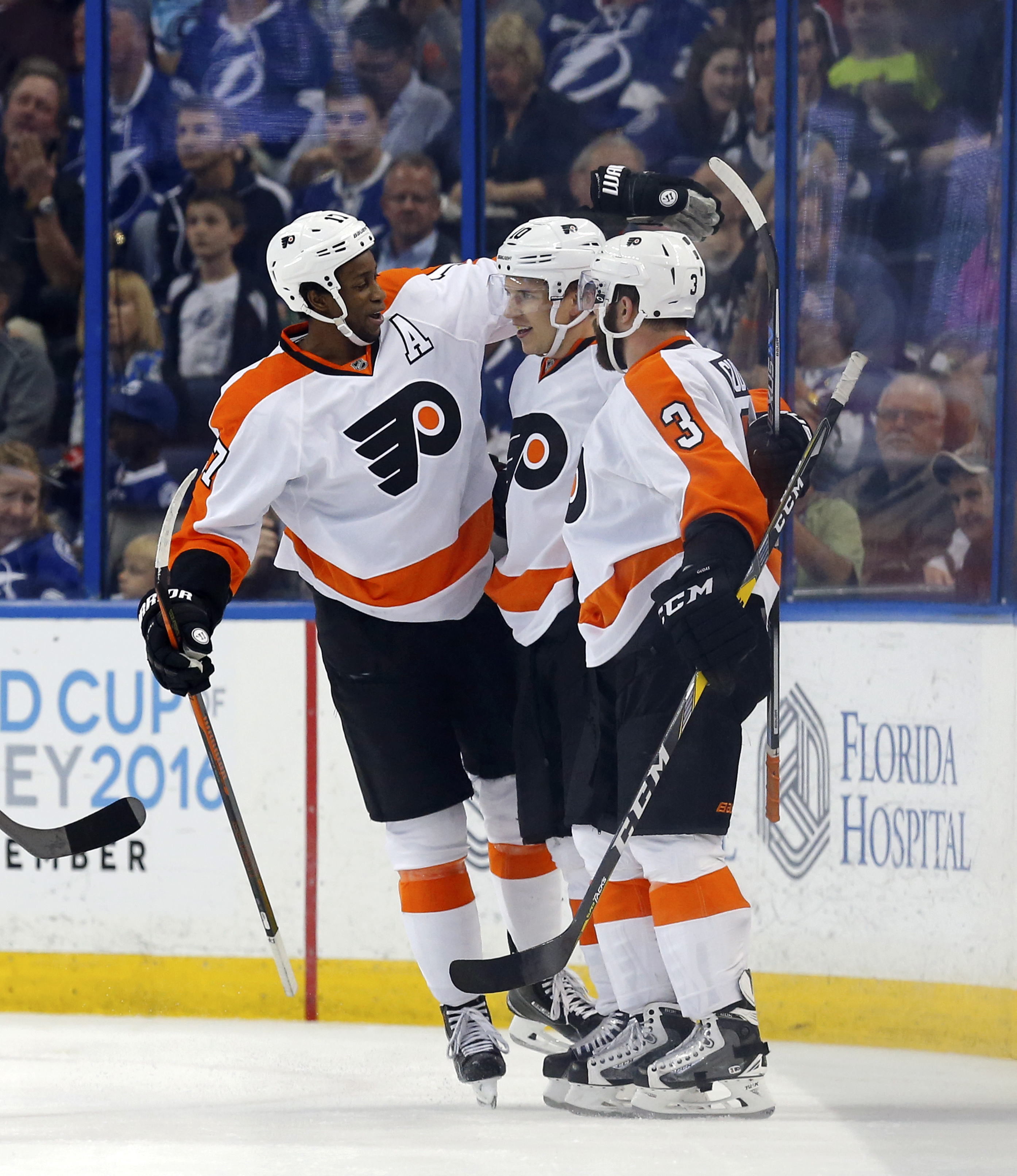 Philadelphia Flyers' Brayden Schenn, center, is congratulated on his goal by teammates Wayne Simmonds, left, and Radko Gudas, of the Czech Republic, during the second period of an NHL hockey game against the Tampa Bay Lightning, Friday, March 11, 2016, in