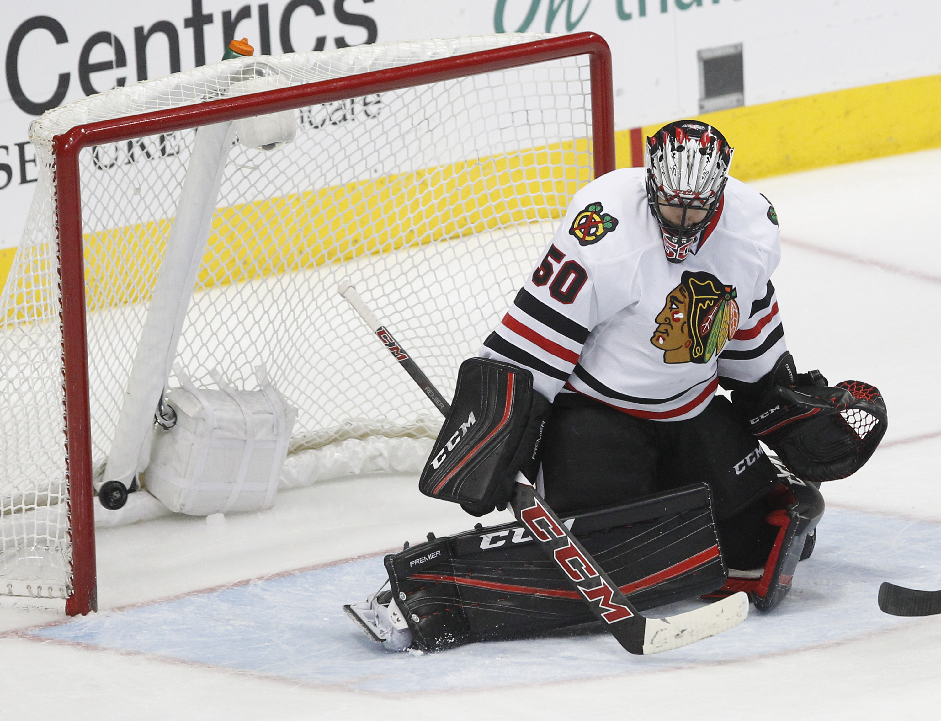 Chicago Blackhawks goalie Corey Crawford looks for the puck as it hits the back of the goal on a shot from Dallas Stars center Jason Spezza during the first period of an NHL hockey game Friday, March 11, 2016, in Dallas. (AP Photo/Tim Sharp)