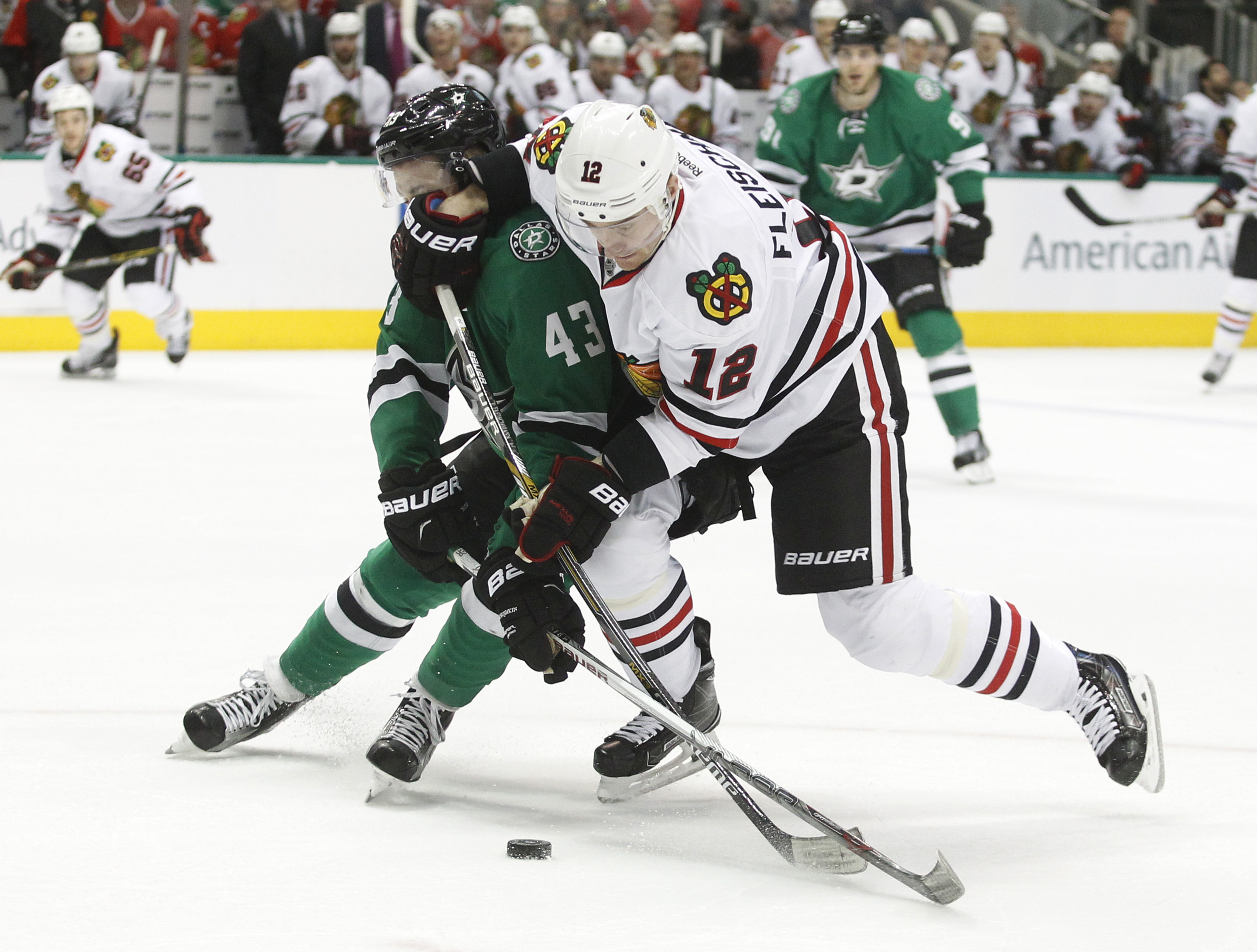 Chicago Blackhawks left wing Tomas Fleischmann (12) and Dallas Stars right wing Valeri Nichushkin (43) battle for the puck during the second period of an NHL hockey game Friday, March 11, 2016, in Dallas.  (AP Photo/Tim Sharp)