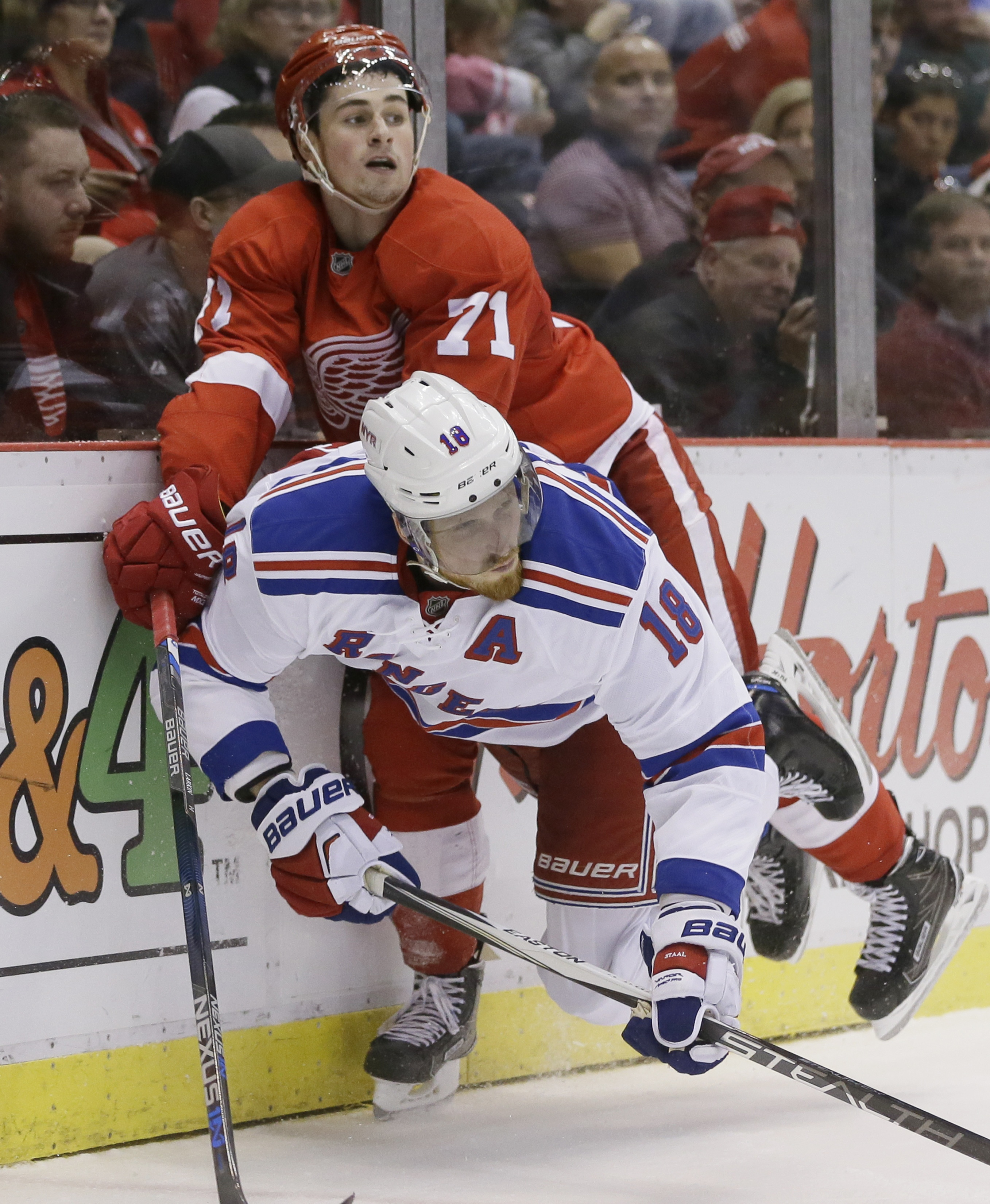 Detroit Red Wings center Dylan Larkin (71) checks New York Rangers defenseman Marc Staal (18) during the second period of an NHL hockey game, Saturday, March 12, 2016, in Detroit. (AP Photo/Carlos Osorio)