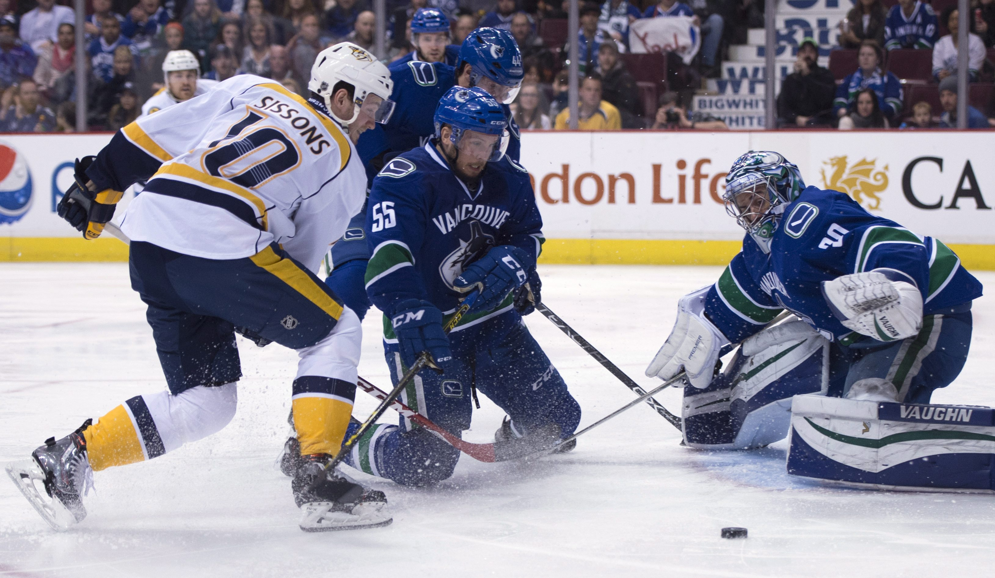 Vancouver Canucks defenseman Alex Biega (55) tries to stop a shot from Nashville Predators center Colton Sissons (10) as Canucks goalie Ryan Miller (30) watches during the first period of an NHL hockey game Saturday, March 12, 2016, in Vancouver, British