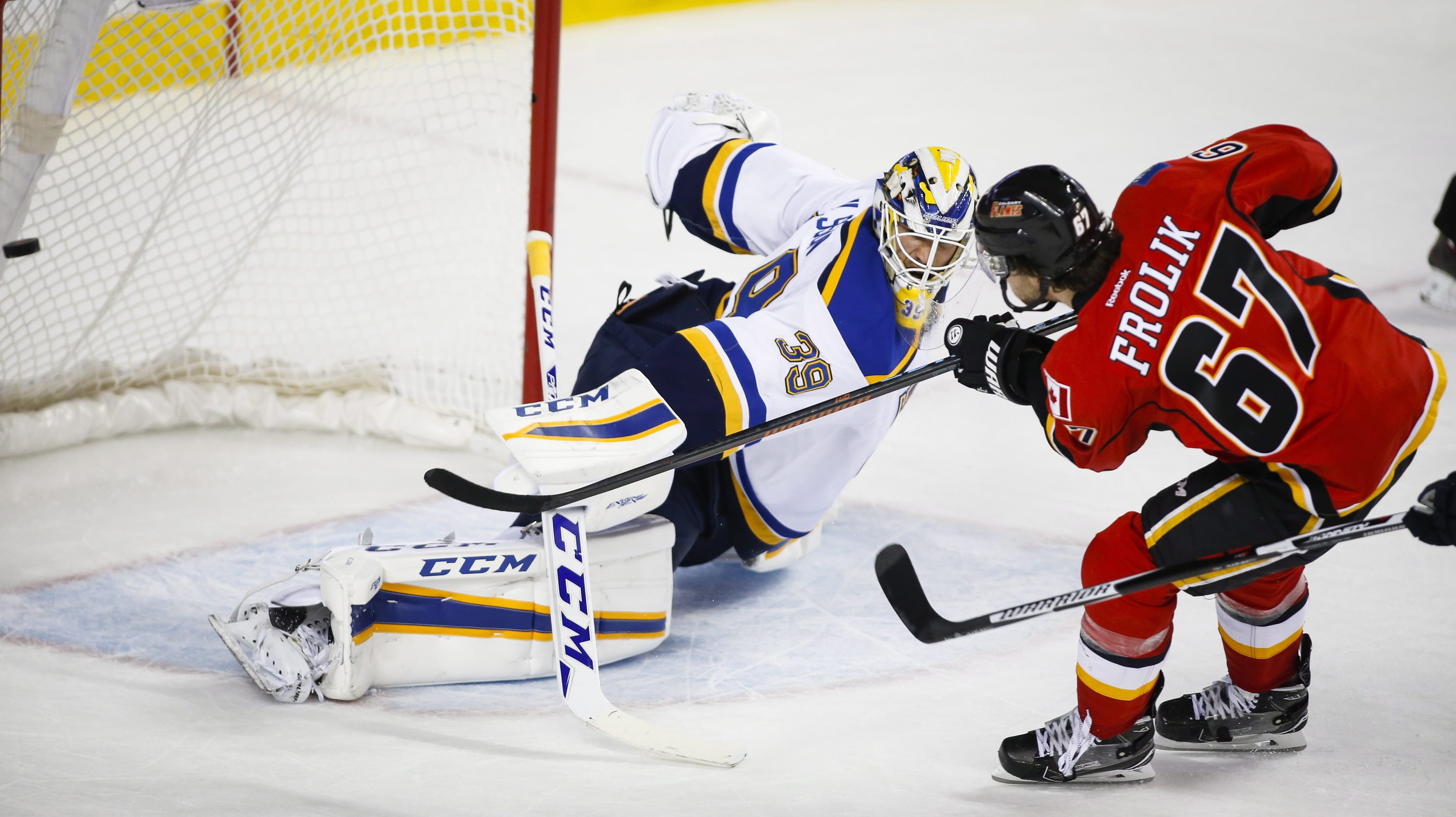 St. Louis Blues goalie Anders Nilsson, left, of Sweden, lets in a goal from Calgary Flames' Michael Frolik, of the Czech Republic, during the third period of an NHL hockey game in Calgary, Alberta, Monday, March 14, 2016. (Jeff McIntosh/The Canadian Press