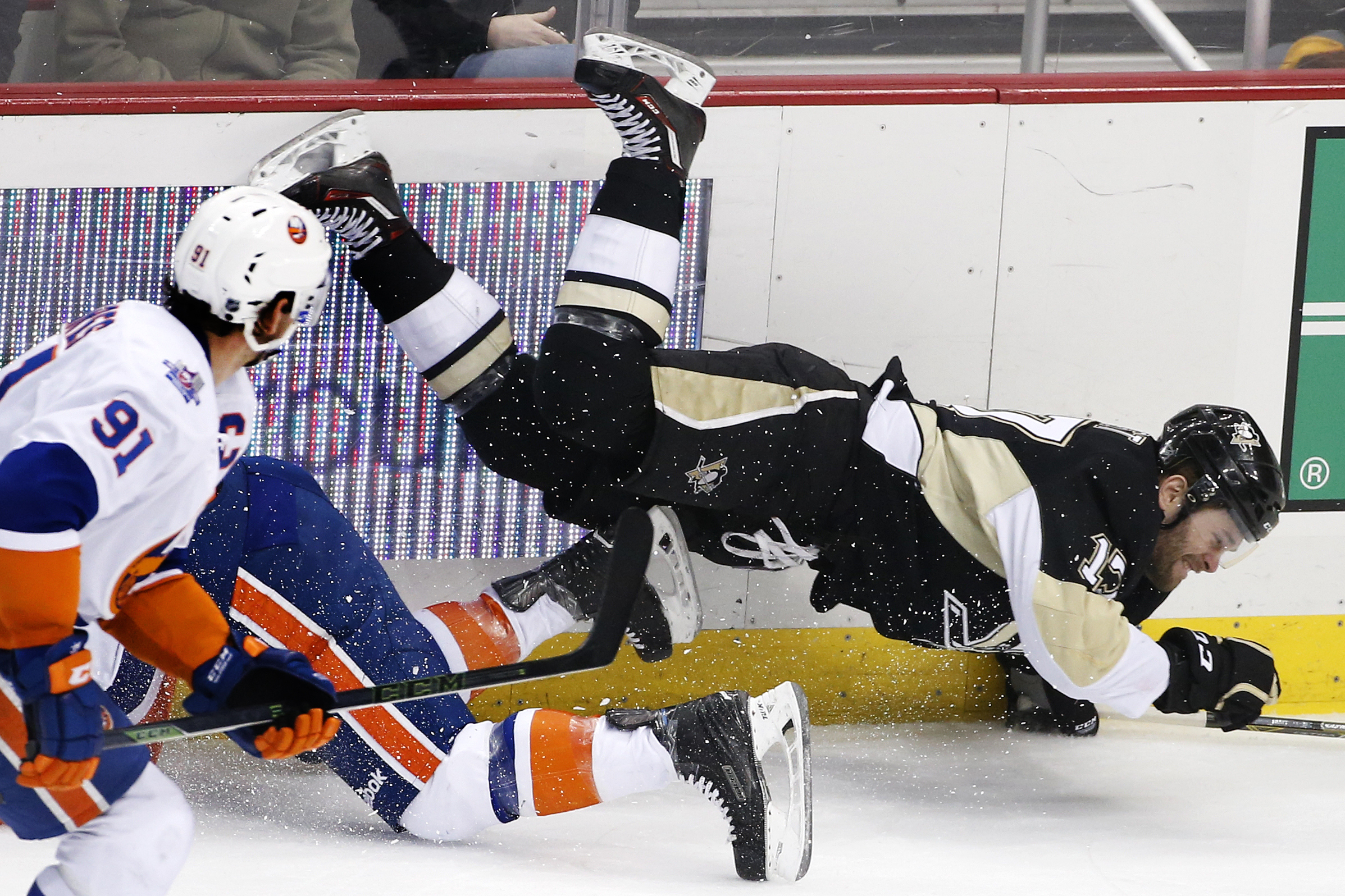 Pittsburgh Penguins' Bryan Rust (17) tumbles after colliding with New York Islanders' Johnny Boychuk, left rear, during the first period of an NHL hockey game in Pittsburgh, Tuesday, March 15, 2016. (AP Photo/Gene J. Puskar)